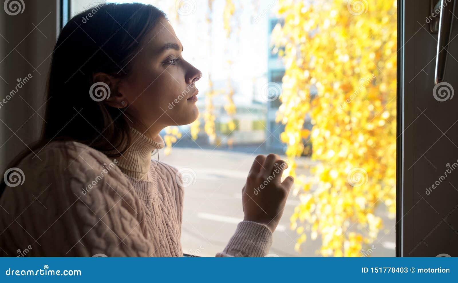 Señora pensativa que mira a través de la ventana, experimentando el desempleo de las dificultades de la vida