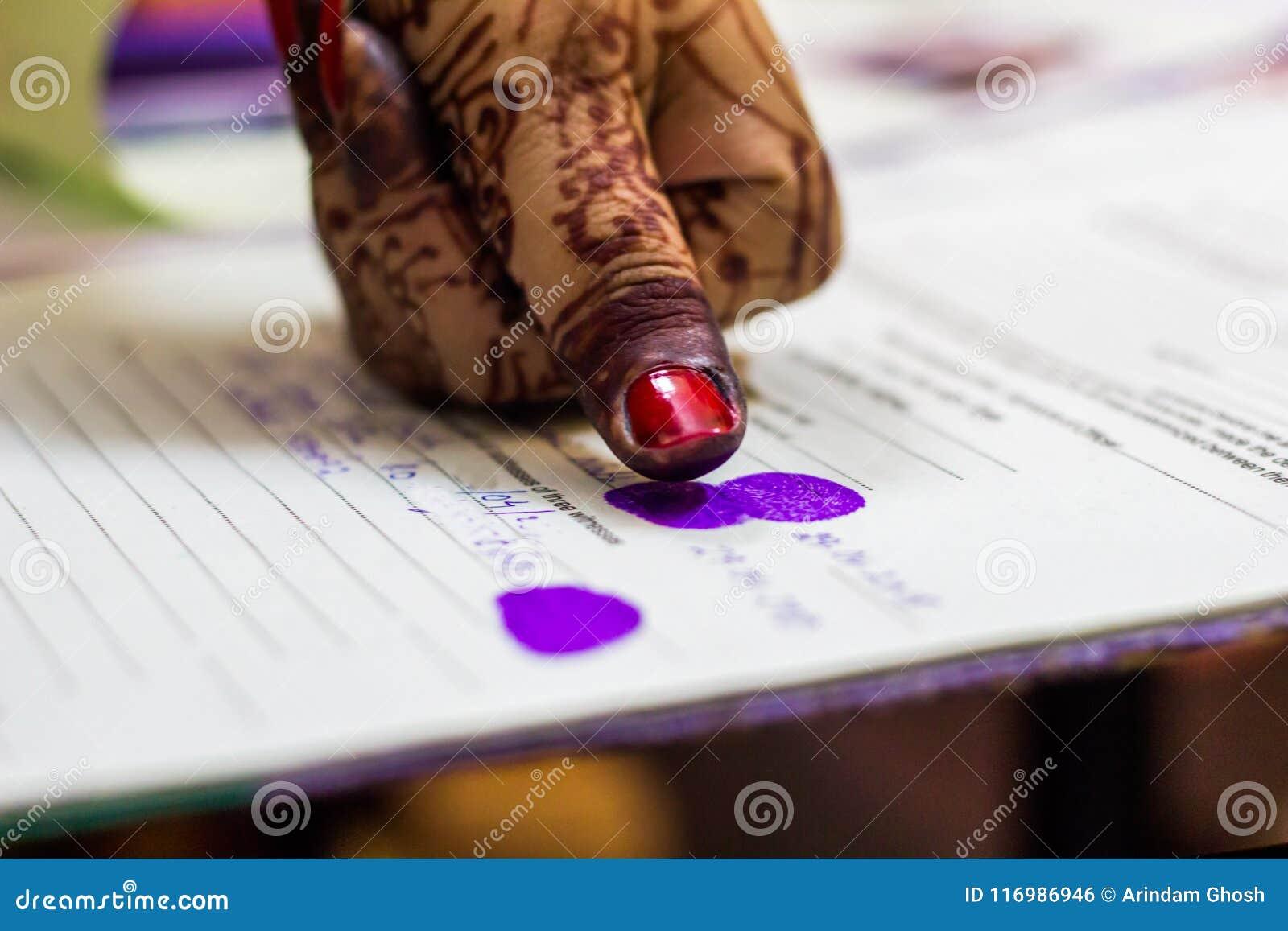 Señora que da la impresión del pulgar en certificado del registro de la boda Matrimonio indio El weddding bengalí
