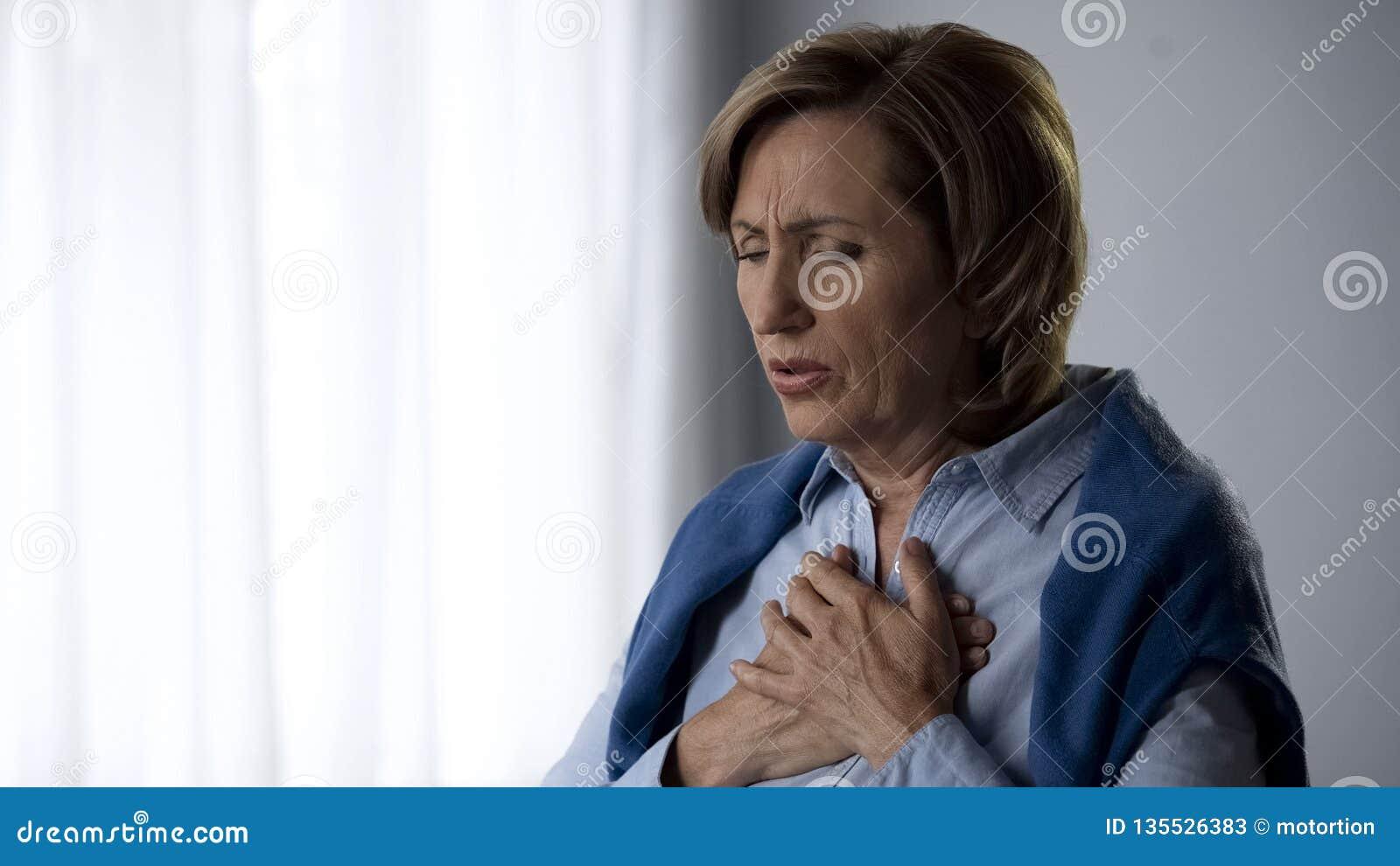 Señora que tiene síntomas del ataque de asma, duros mayores a la respiración y al dolor en pecho