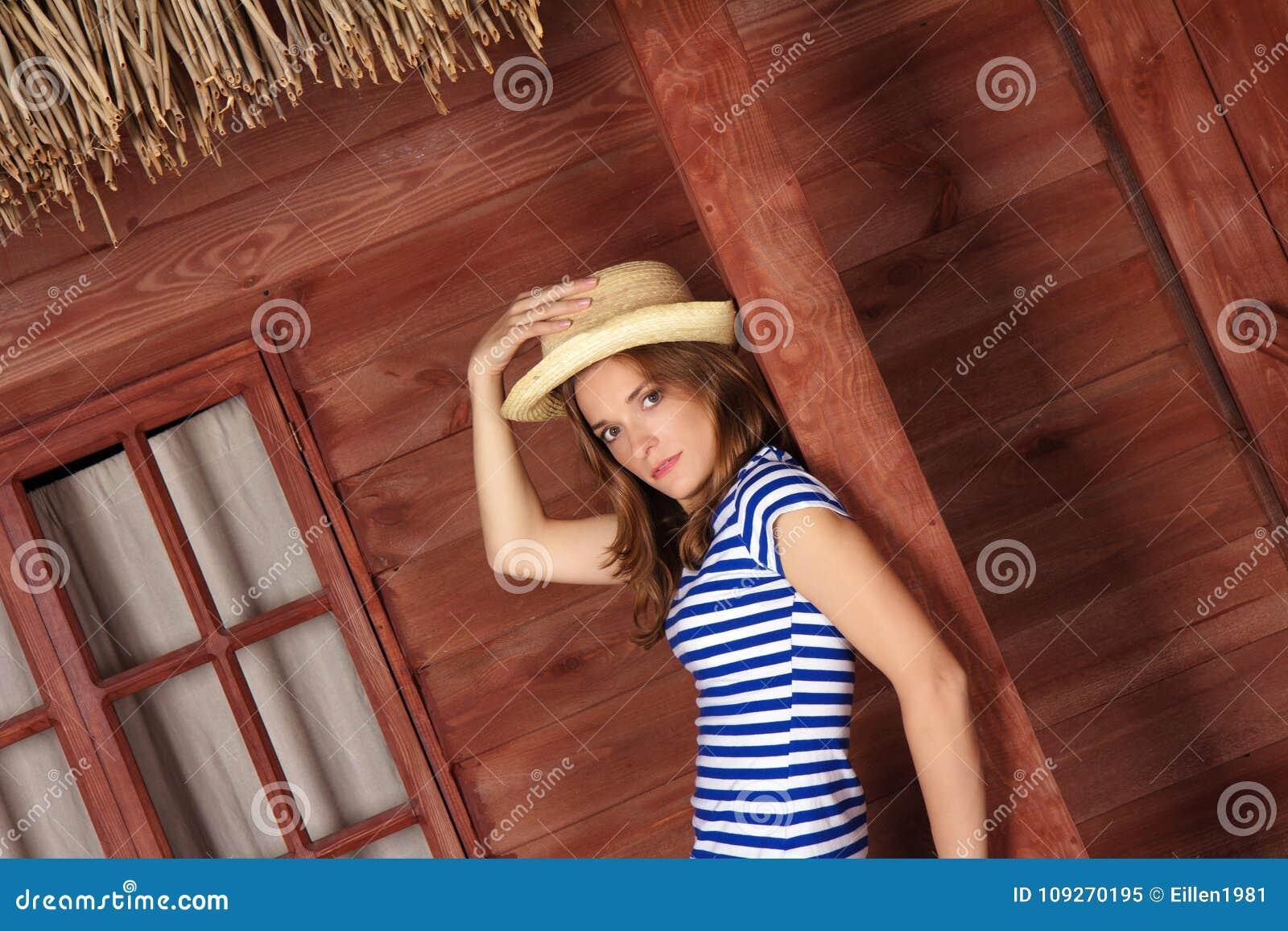Señora rubia con el sombrero de paja cerca de la casa de madera en tiempo de verano