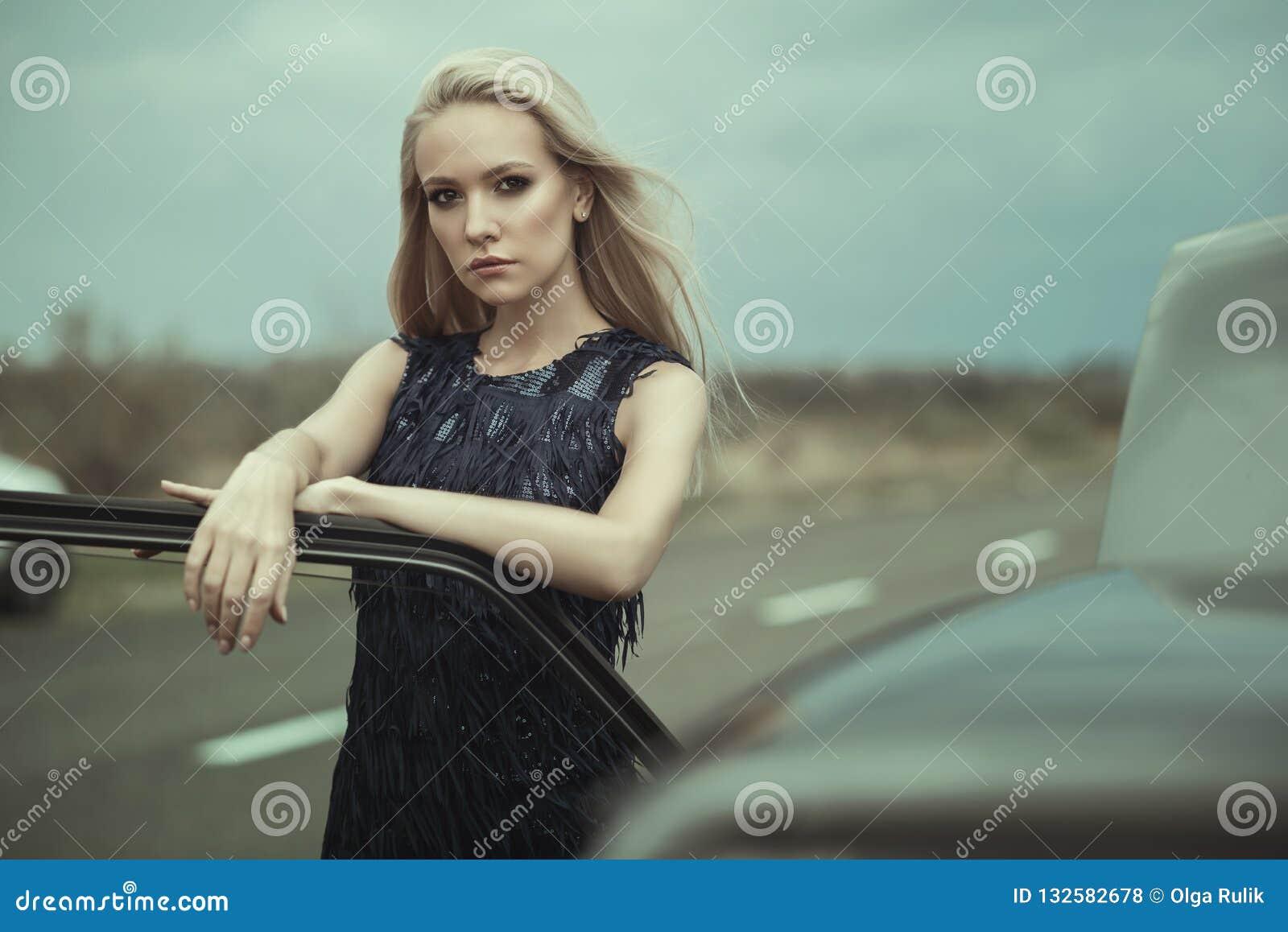 Señora rubia hermosa en la situación azul marino lujosa del vestido de noche de la borla de la lentejuela en su coche viejo con l