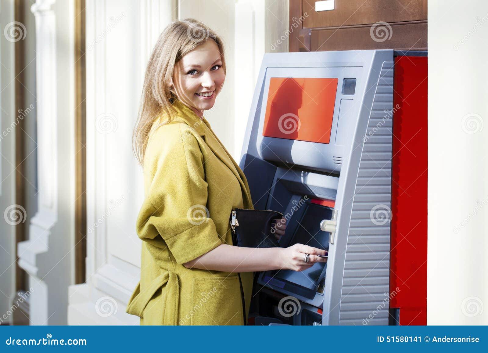 Señora rubia que usa una máquina del cajero automático