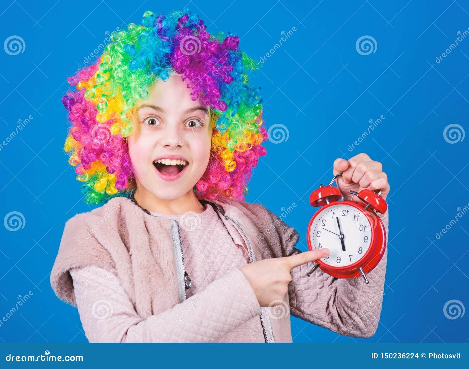 Se concentrer sur l exactitude Petit enfant heureux se dirigeant au r?veil Peu fille souriant avec l horloge Exactitude et soin