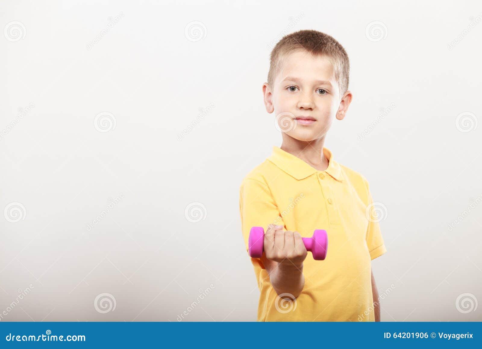 Se divierte al muchacho que hace ejercicio con pesa de gimnasia