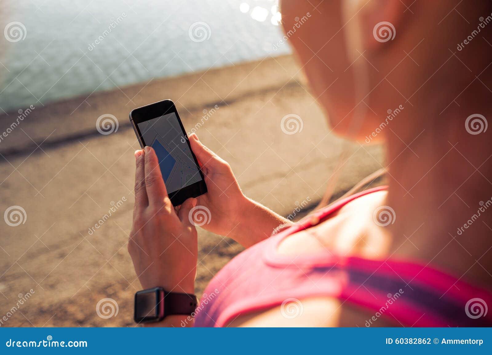Se divierte a la mujer que usa el teléfono elegante