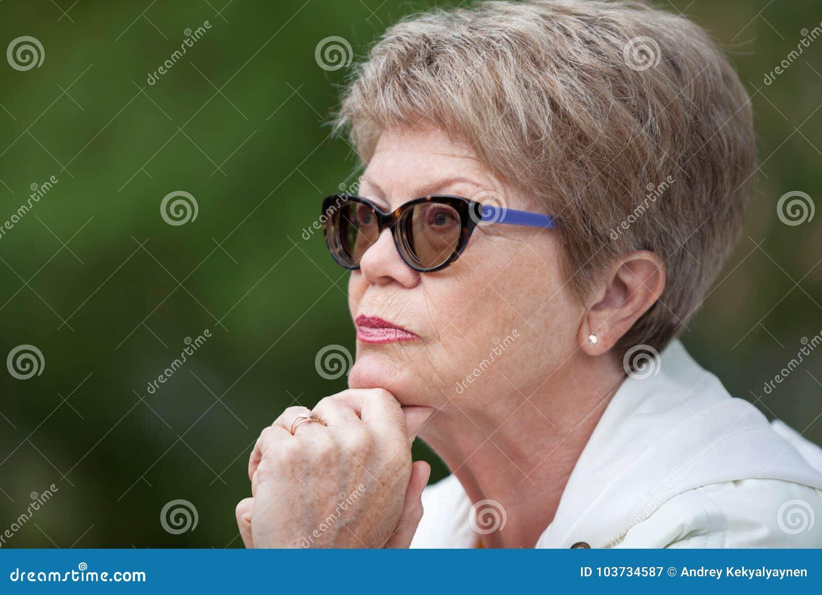 Se ferme vers le haut du portrait de vue de côté d une femme agée en verres pensant avec la main sous la tête
