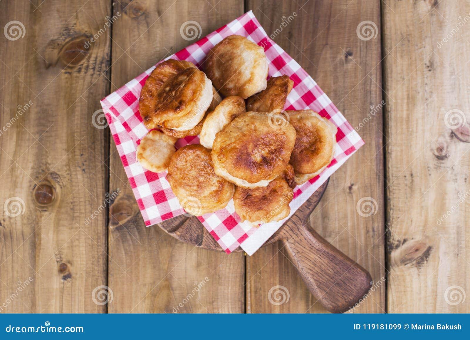 Se fríen los anillos de espuma dulces Comida hecha en casa Servilleta en jaula roja Fondo de madera Copie el espacio Endecha plan
