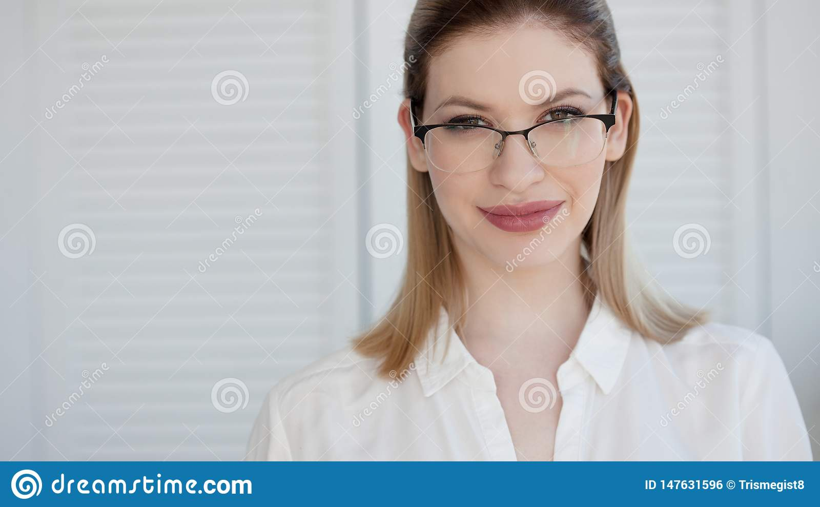 Se?ora joven del negocio en la camisa y los vidrios blancos Sonrisa atractiva de la mujer joven