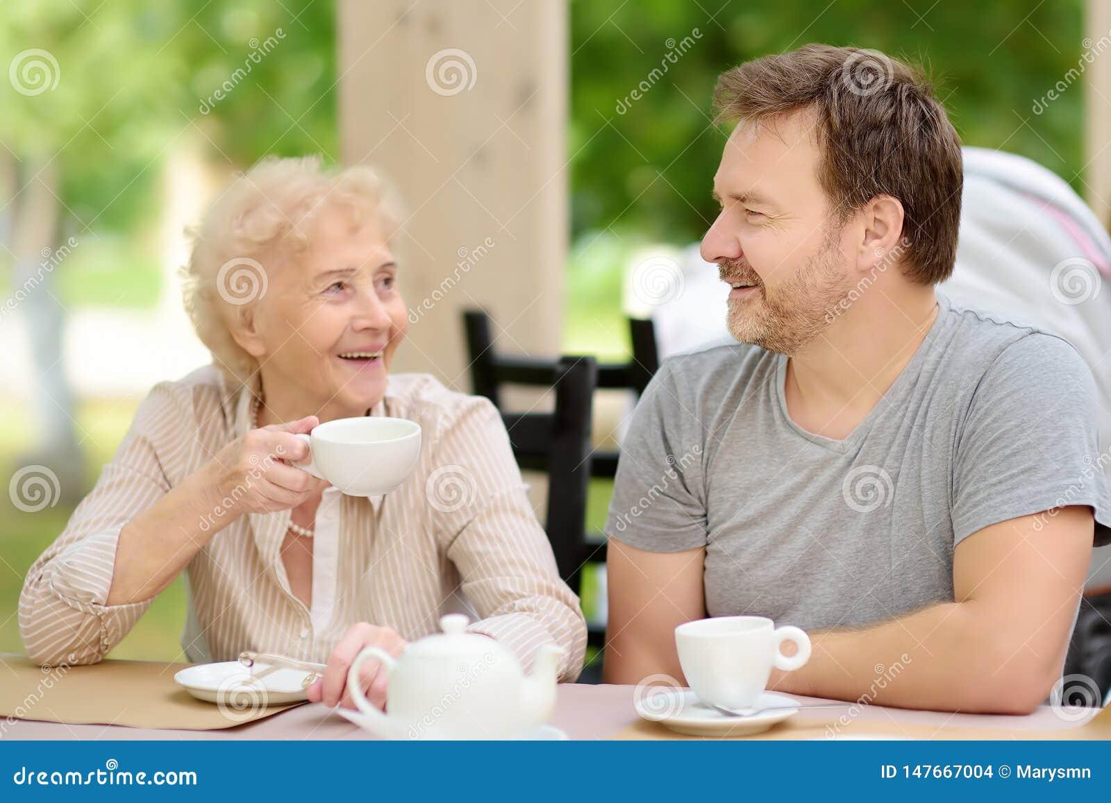 Se?ora mayor hermosa con su t? de consumici?n del hijo maduro en caf? o restaurante del aire libre Forma de vida mayor de la se?o