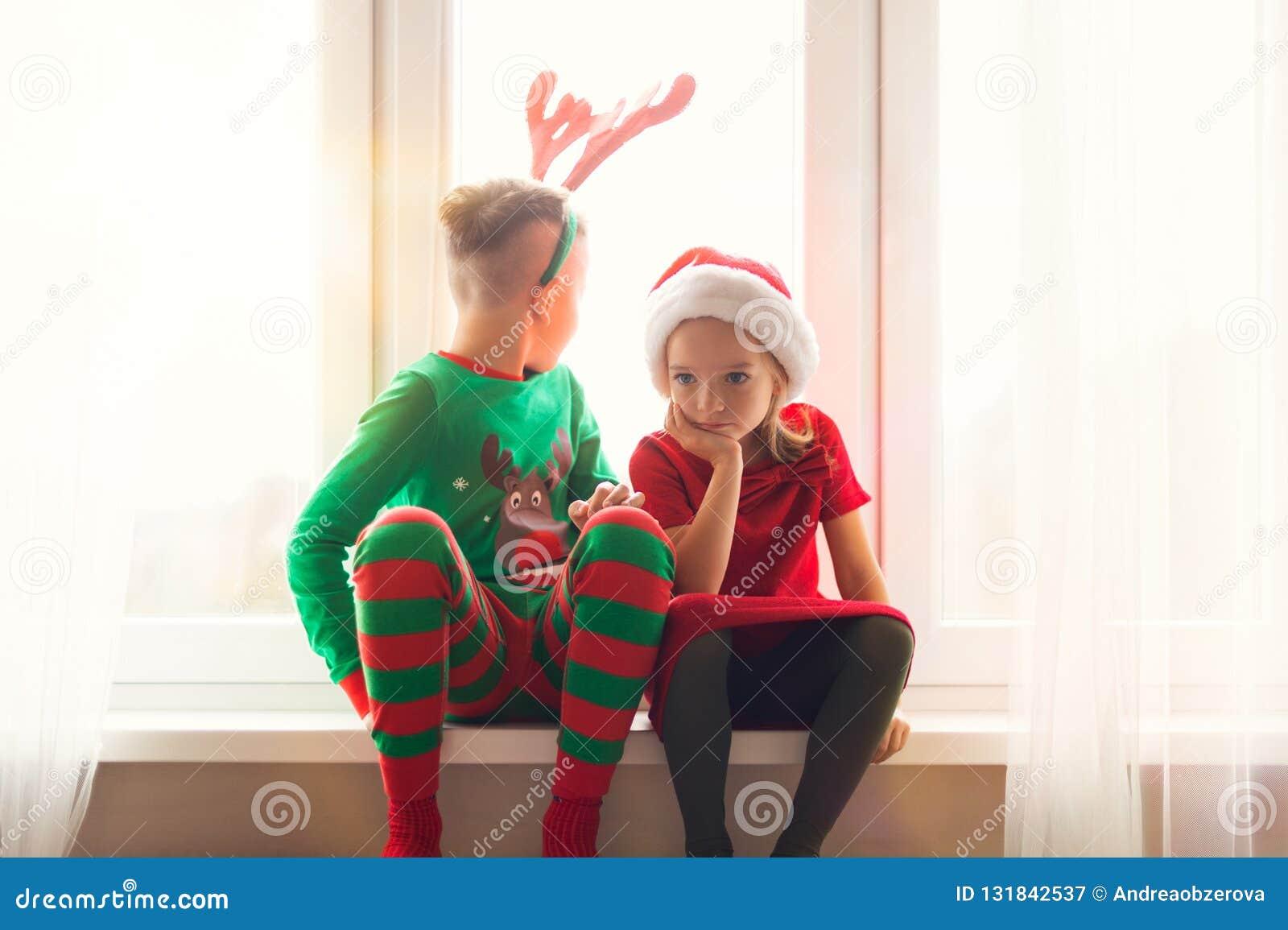 Se reposer de frère et de soeur agité sur le filon-couche de fenêtre au temps de Noël, regardant la fenêtre, Santa Claus impatiem