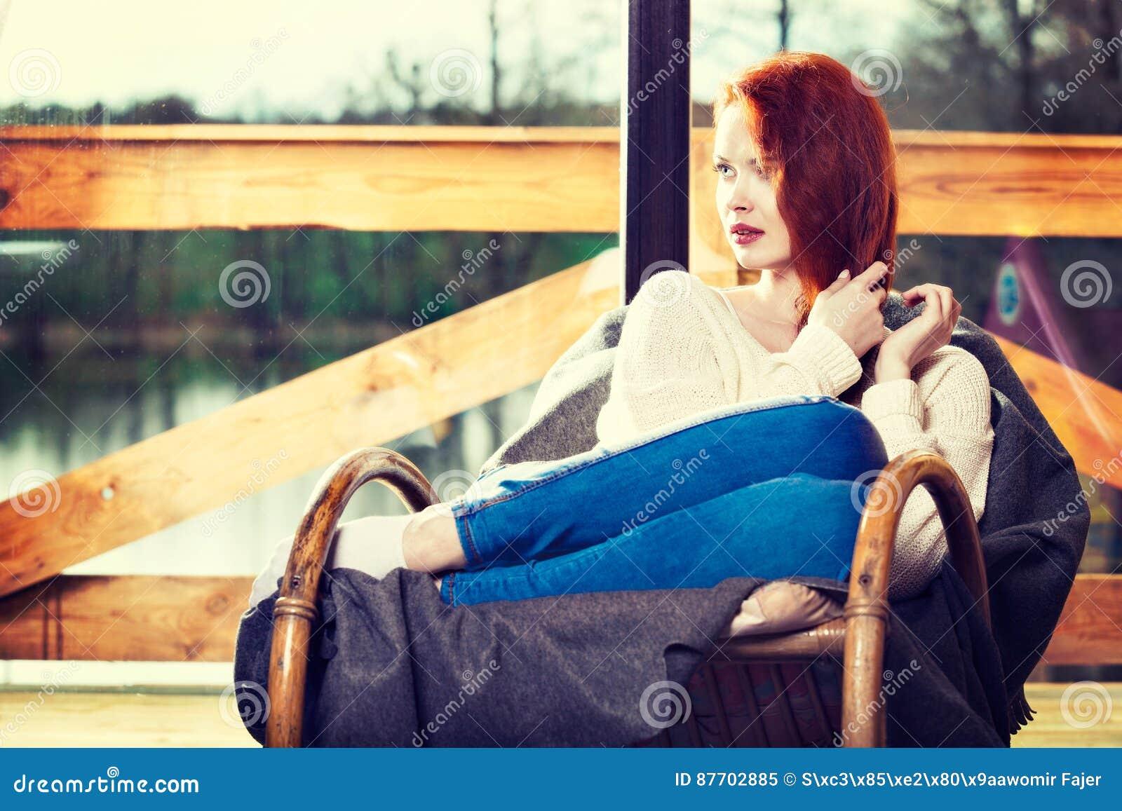 Se reposer de repos de femme rousse d Atractive sur la chaise de basculage dans f