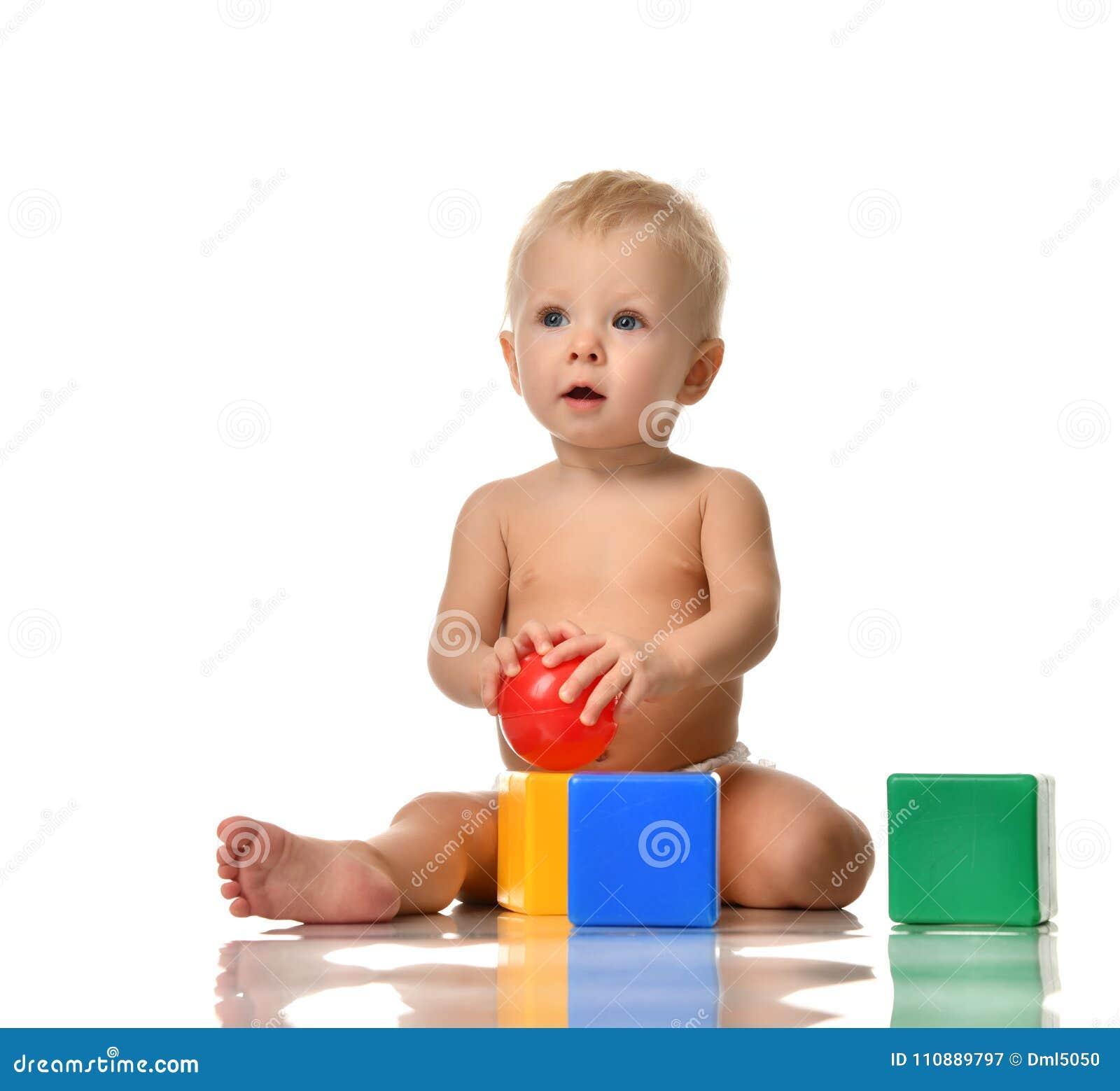 6c0b6023ab05c Se reposer infantile d enfant en bas âge de bébé d enfant nu dans la couche-culotte  avec le jouet vert-bleu de brique et jouer rouge de boule d isolement ...