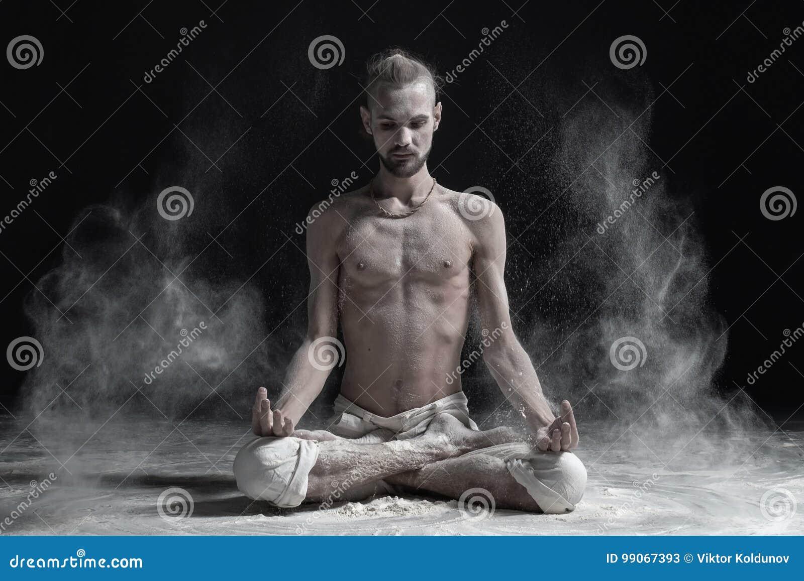 Se reposer méditant de jeune homme serein sportif dans en tailleur la pose de lotus de yoga, Padmasana avec des paumes dans le mu