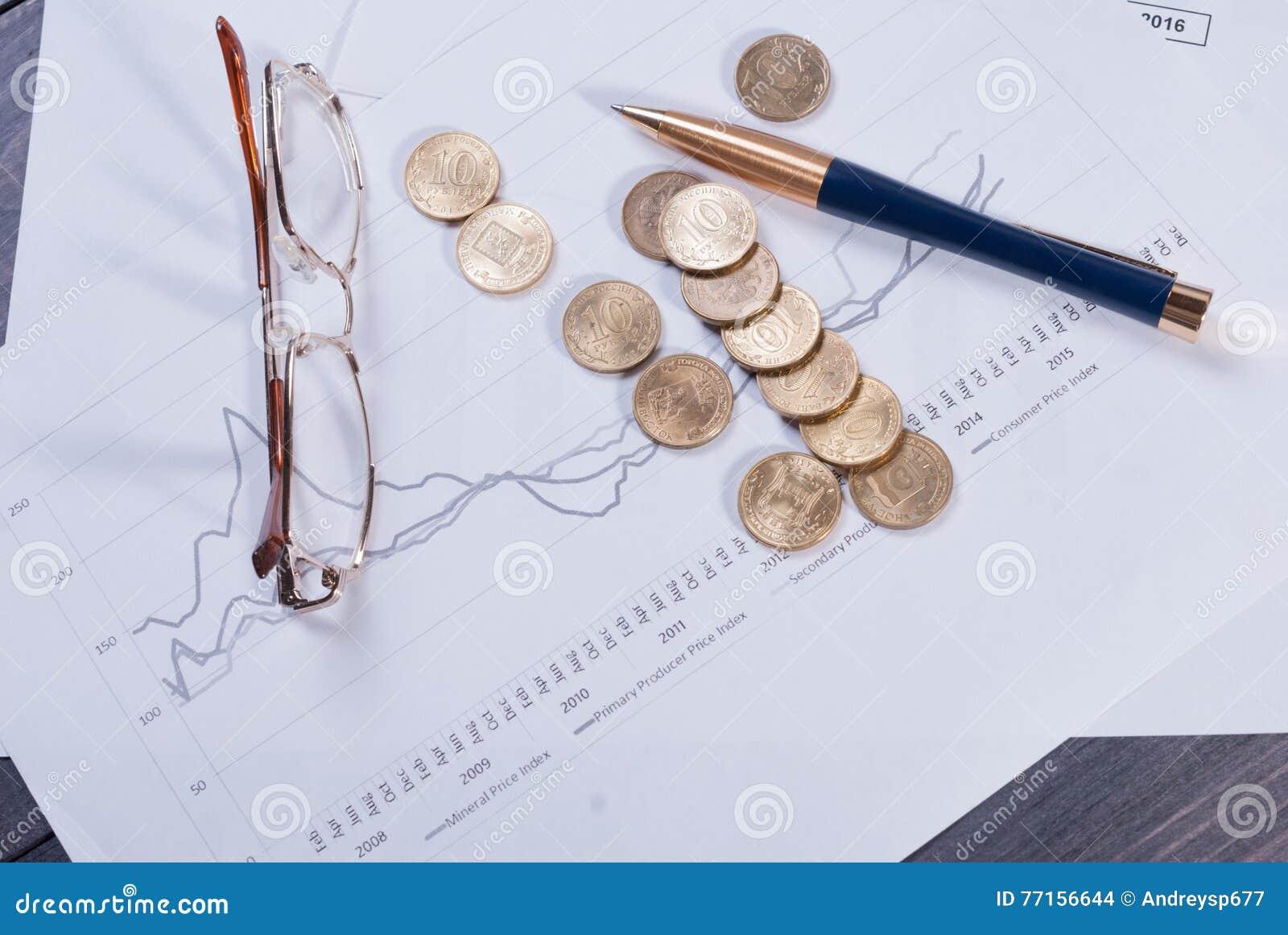 Se trouvant sur les verres financiers de diagrammes, le stylo et les pièces de monnaie dispersées