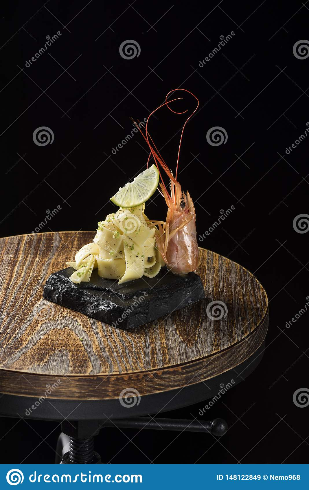Sea carbonara with lemon and prawns on wood