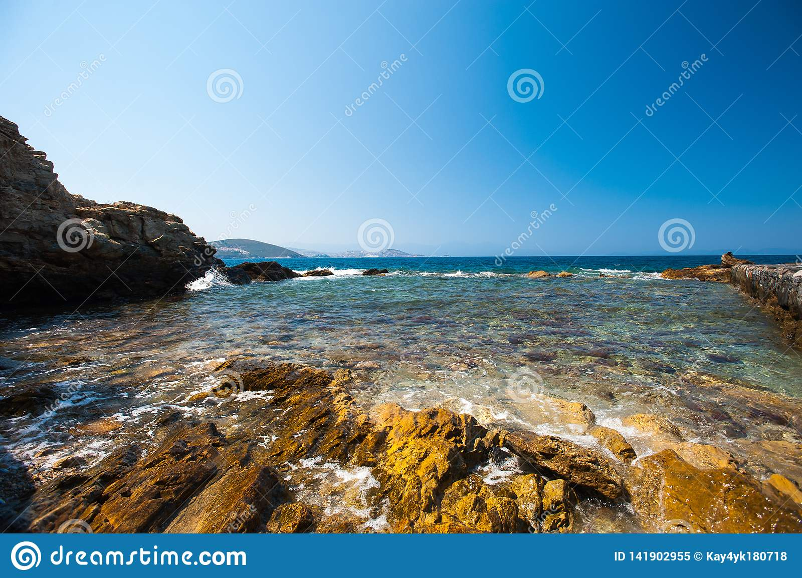 The sea beats on the rocks. clear water on the shore