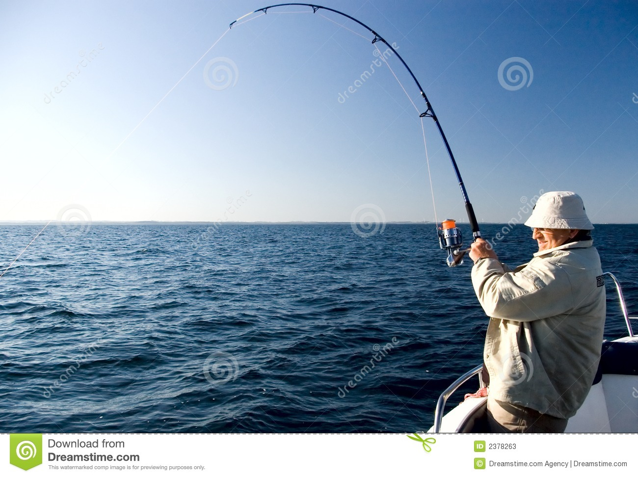man with a fishing rod, pulling his line hard. There is obviously a ...