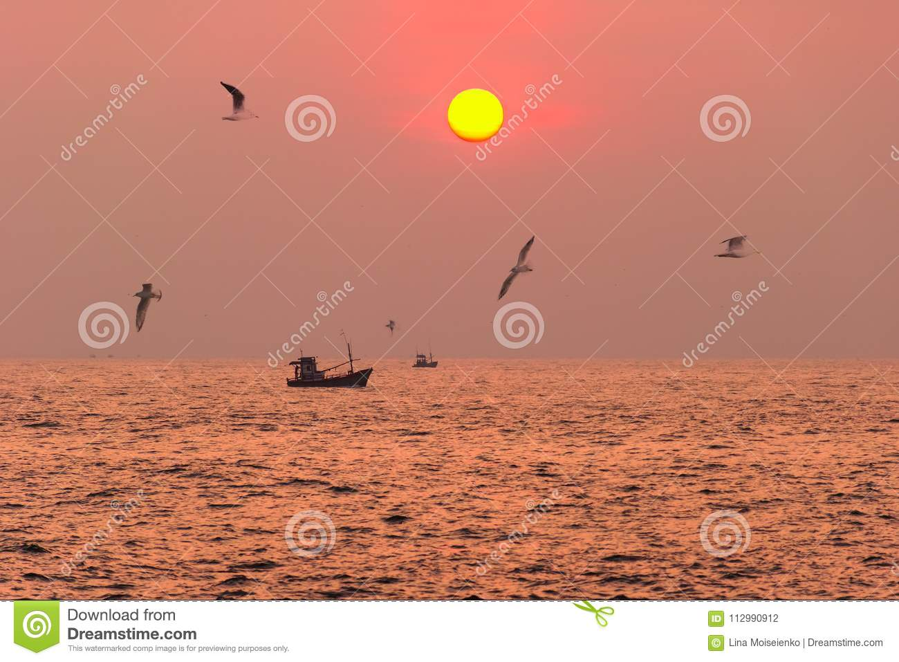 Sea landscape at sunset time with fishing boat on the horizon and birds