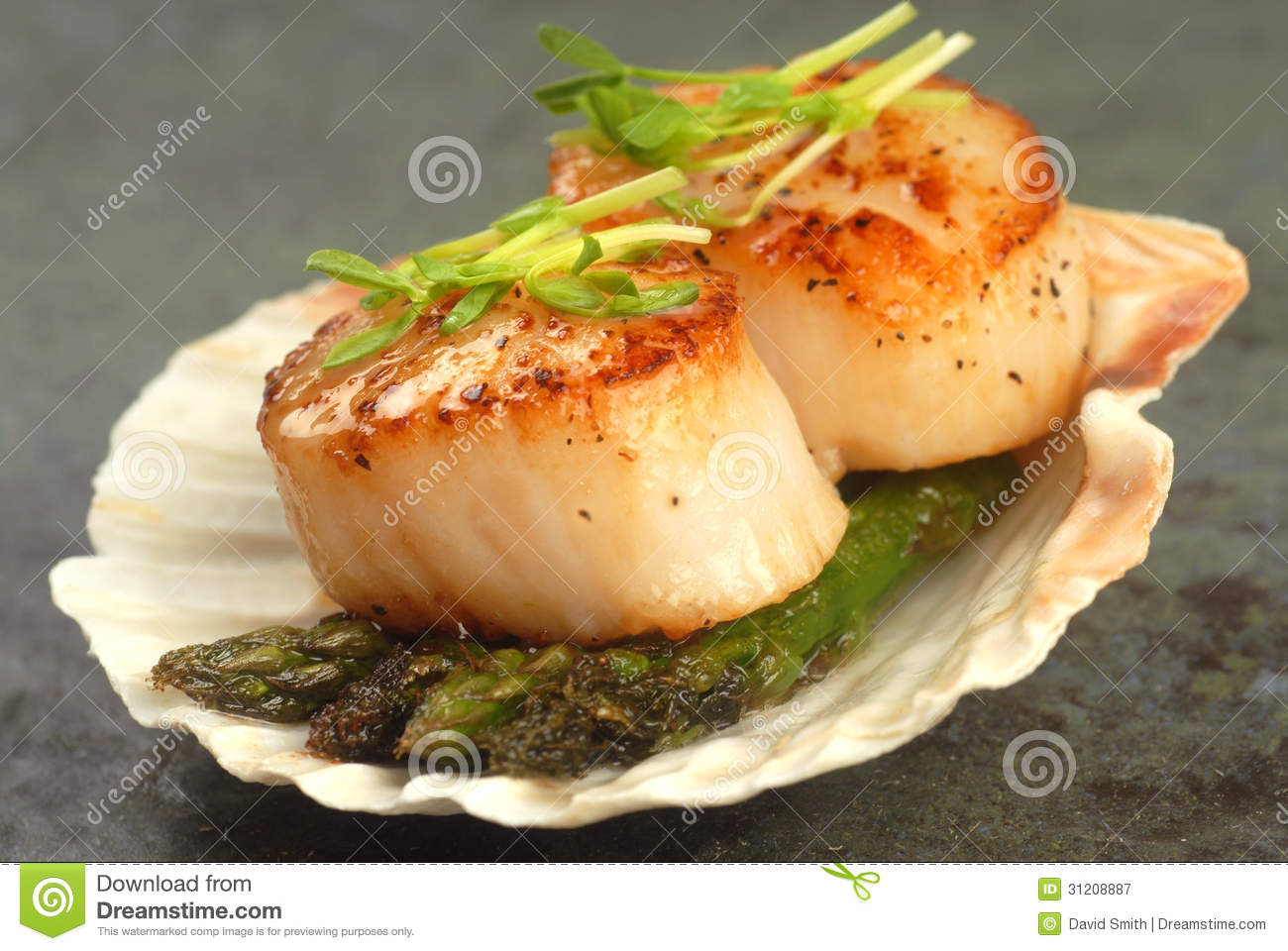 ... sea scallop with asparagus and pea shoots served on a scallop shell