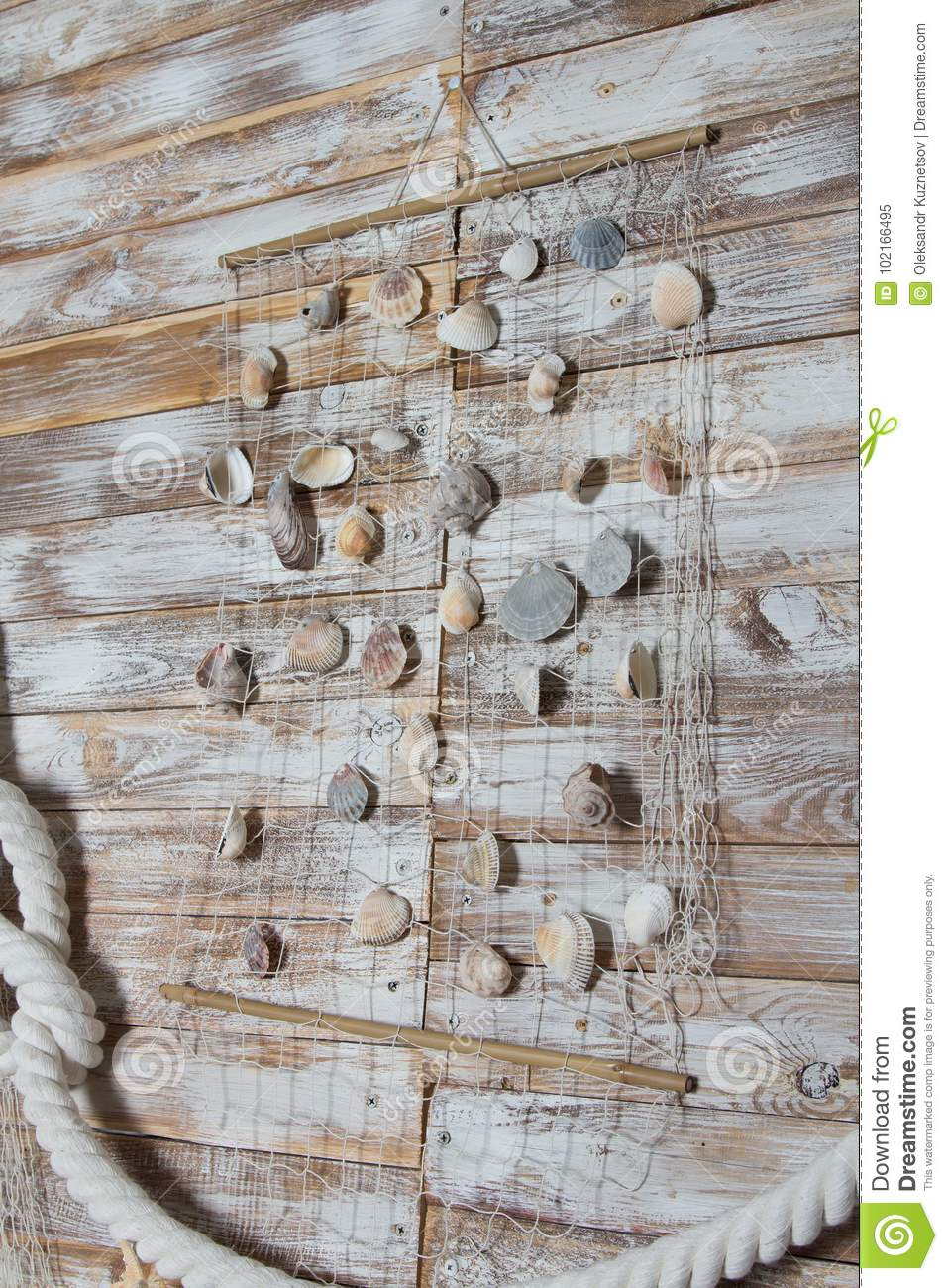 Sea shells in a fishnet,on wooden board, summer vacation background