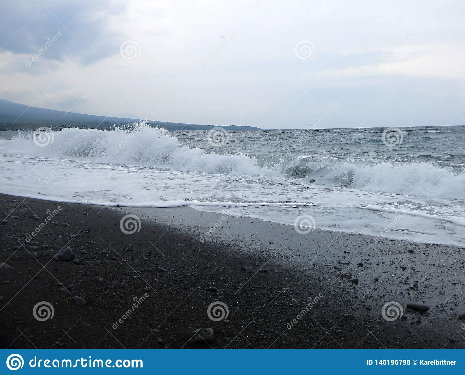 Waves, surf and sea foam hitting the sandy black volcanic sand beach of Bali. In Amed, the sea is quiet, but the waves around the