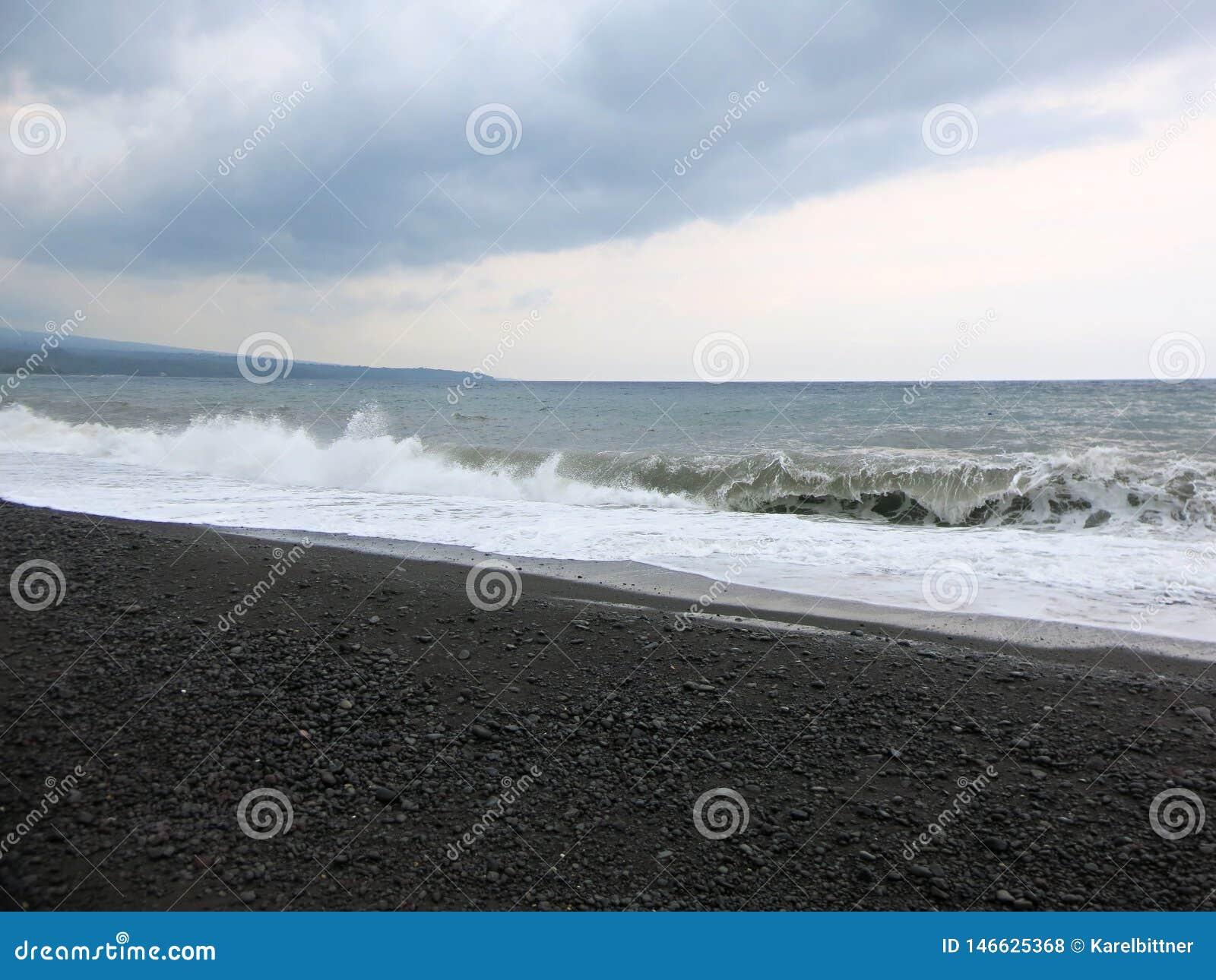 Sea surf and waves crashing against a black sand beach in Bali.