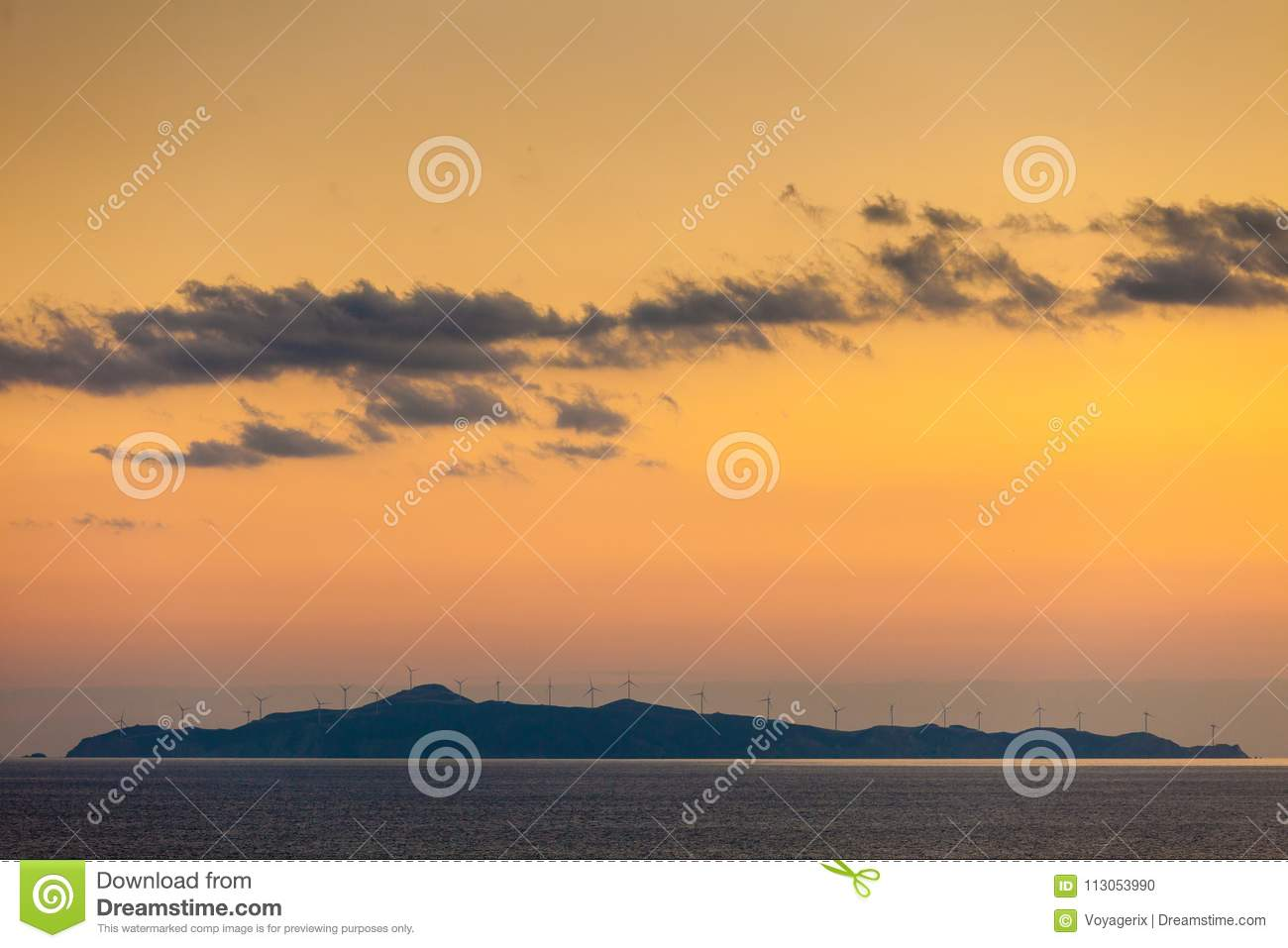 Sea view with wind turbines farm at sunset