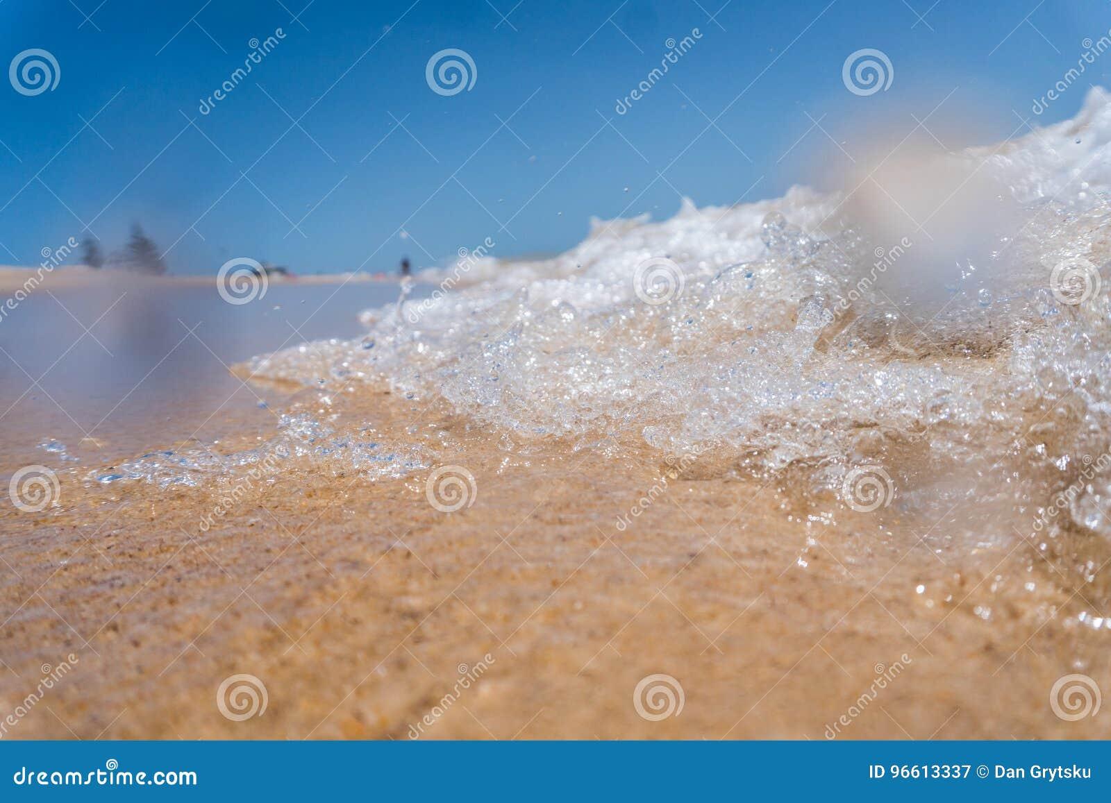 Sea wave close up near beach on sand
