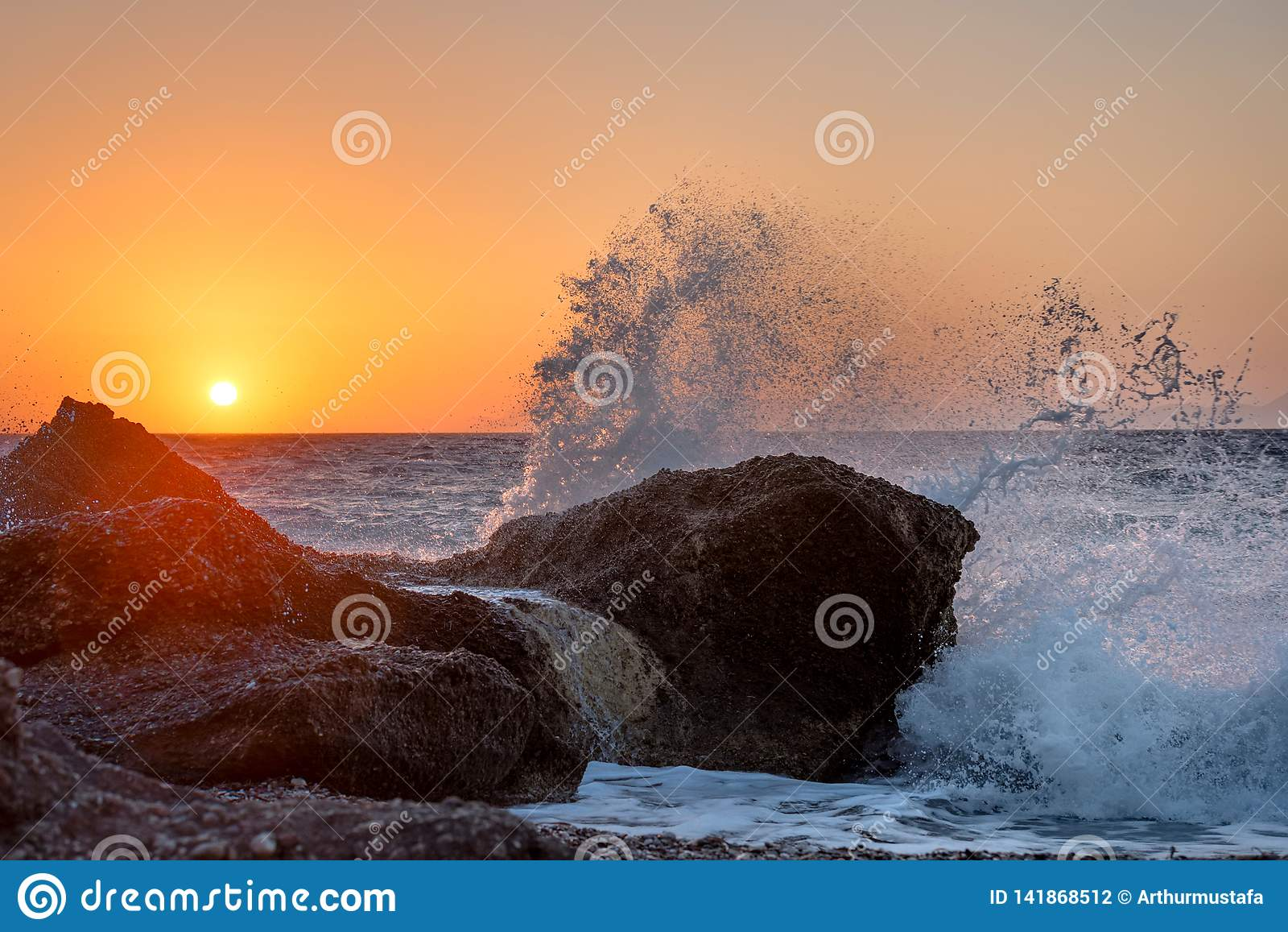 Sea waves crushing and splashing on the rocks on a tropical beach, in beautiful warm sunset light