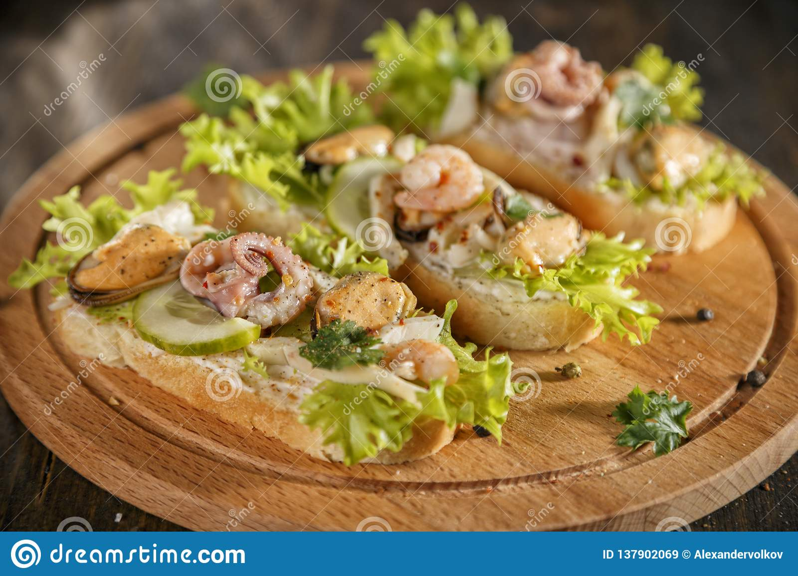 Seafood bruschetta topped with fresh salad, shrimp, octopus, mussel