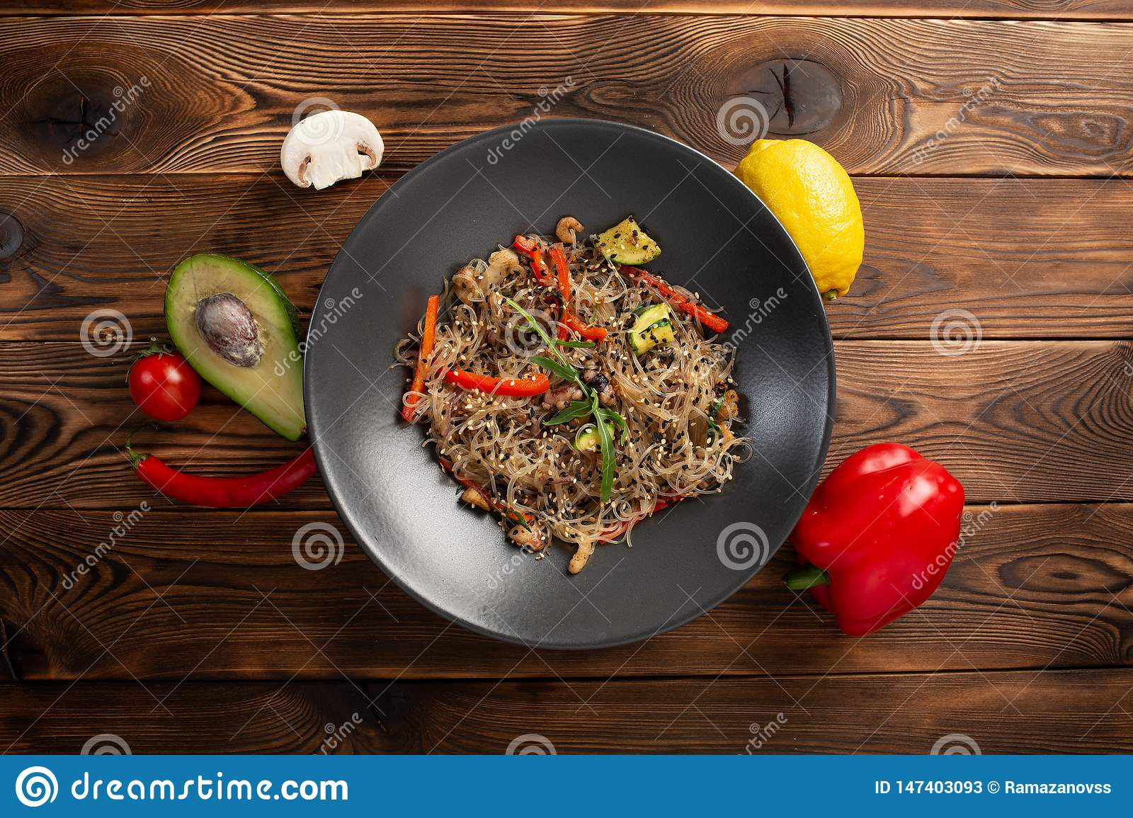 Seafood noodle chow in black plate on wooden background