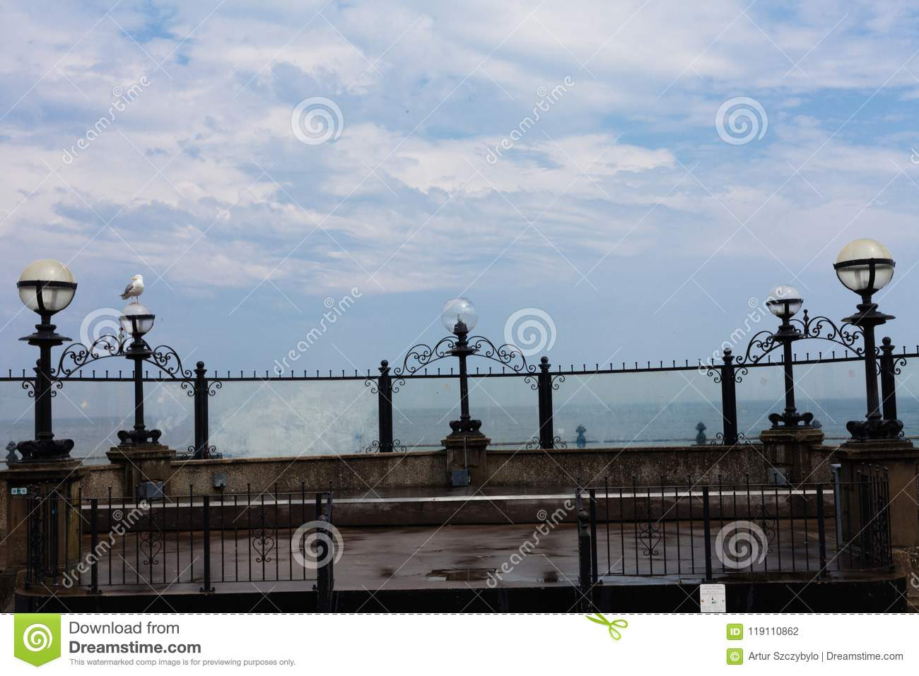 Seagull sits on the shore.Ocean waves hitting the seashore. Blue sky with clouds in the background. Light lamps on the seashore. C