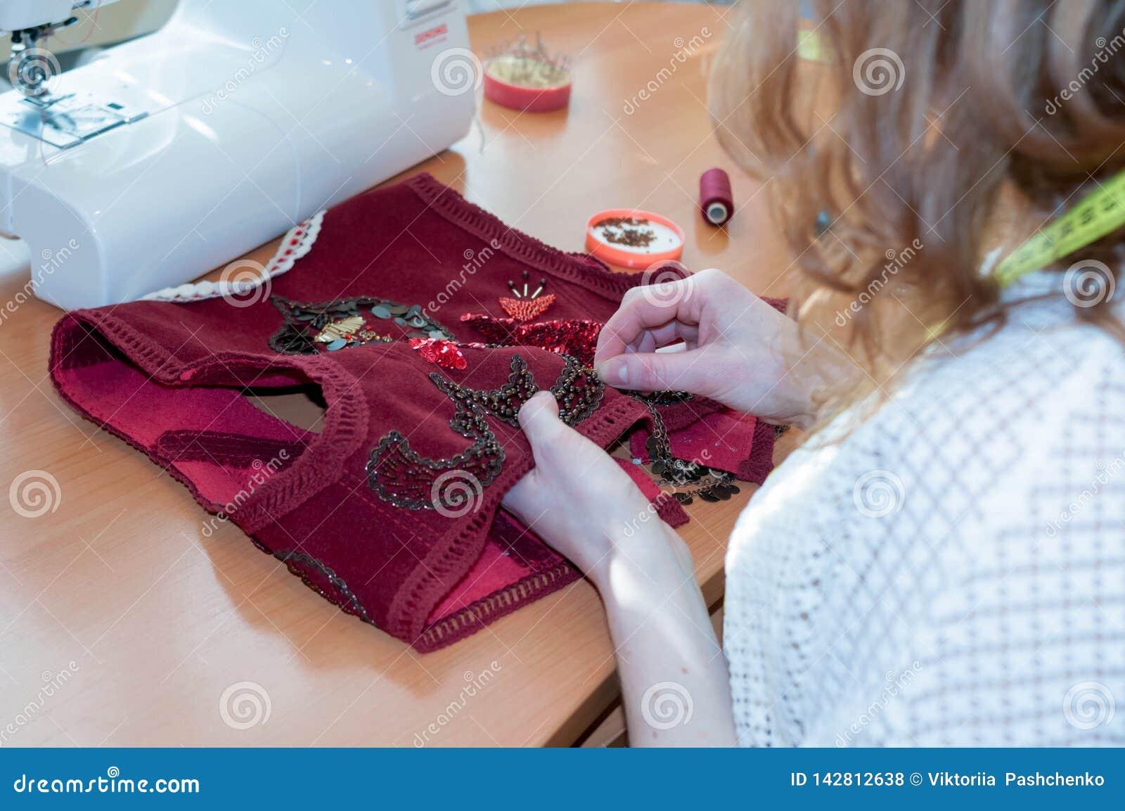 Seamstress η συνεδρίαση στον πίνακα με τη ράβοντας μηχανή και κεντά την κόκκινη φανέλλα στο στούντιο