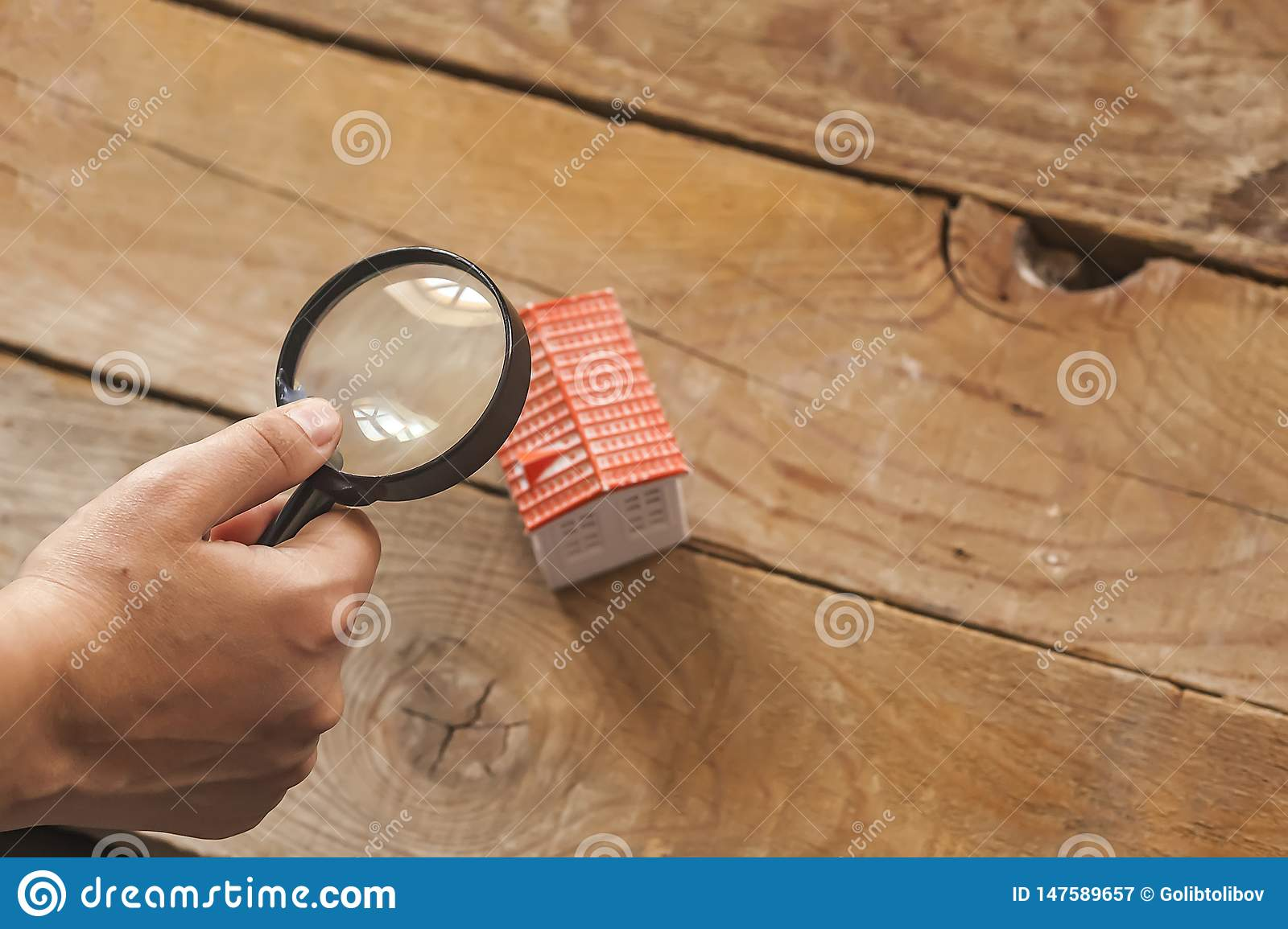 Searching a new home, real estate concept. Man looking to miniature toy house through a magnifying glass, Buy or sell the property