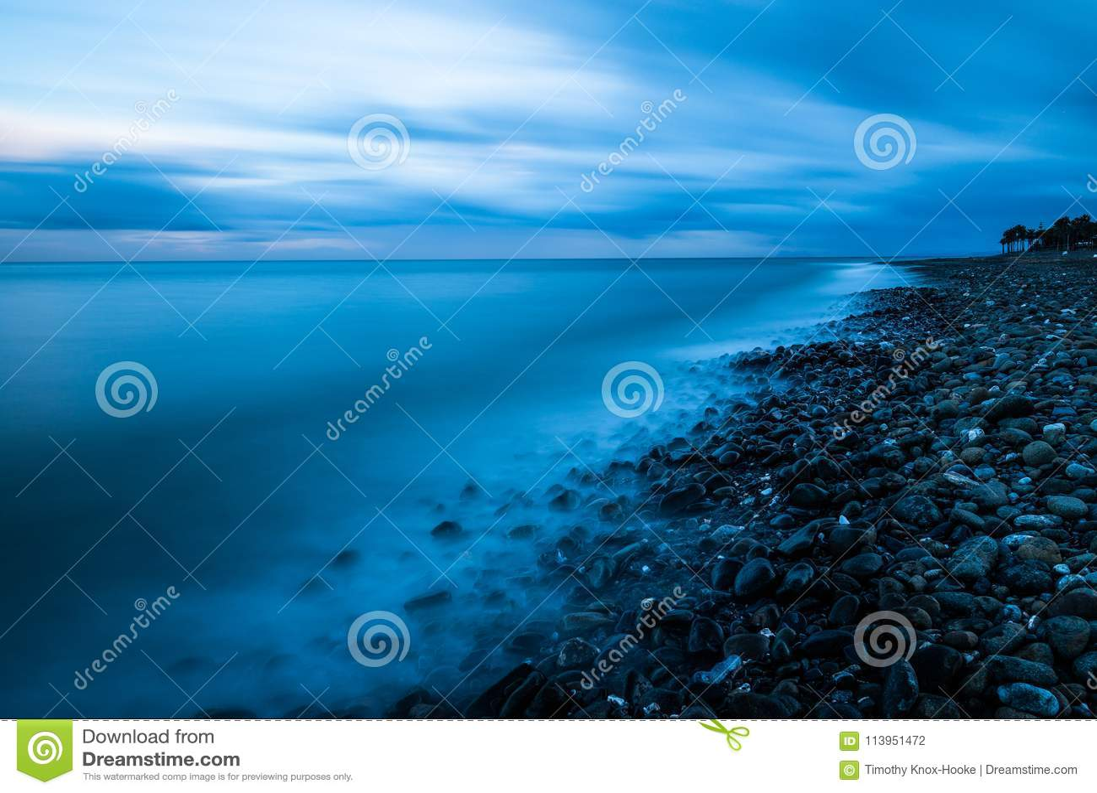 Seascape χαλικιών παραλιών ηλιοβασίλεμα