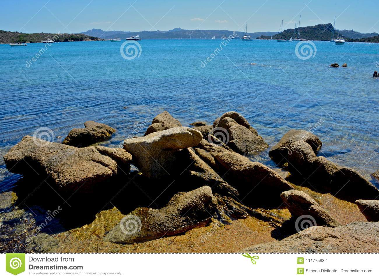 Seascape with blue sea,sky rocks formation and some boats moored