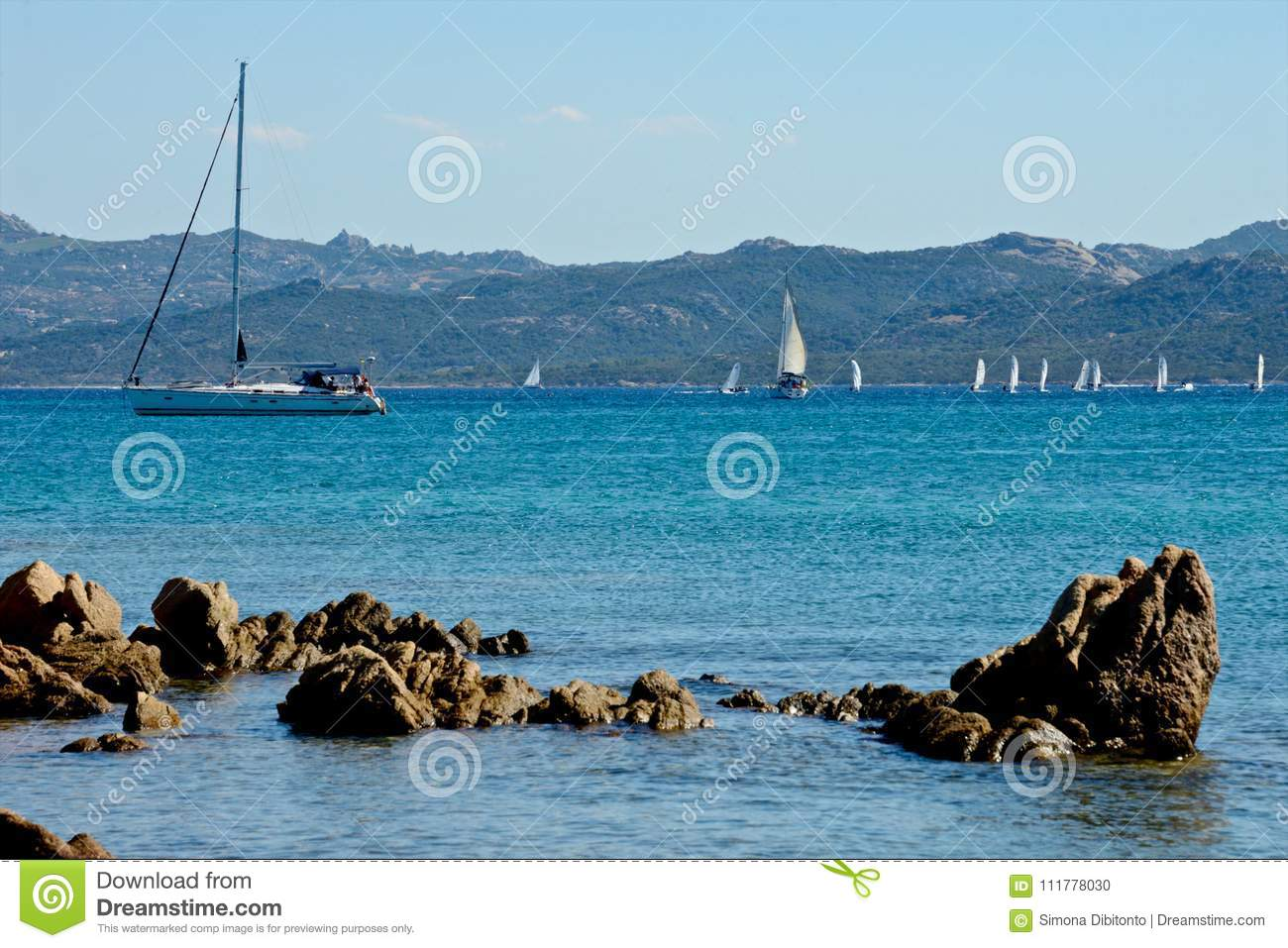 seascape with blue sea and some rocks and yachts moored