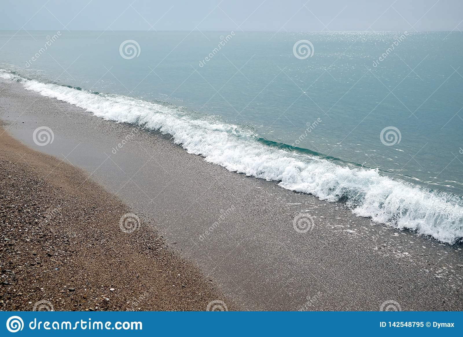 Seascape with calm sea surf with waves and sun reflecton on water on skyline