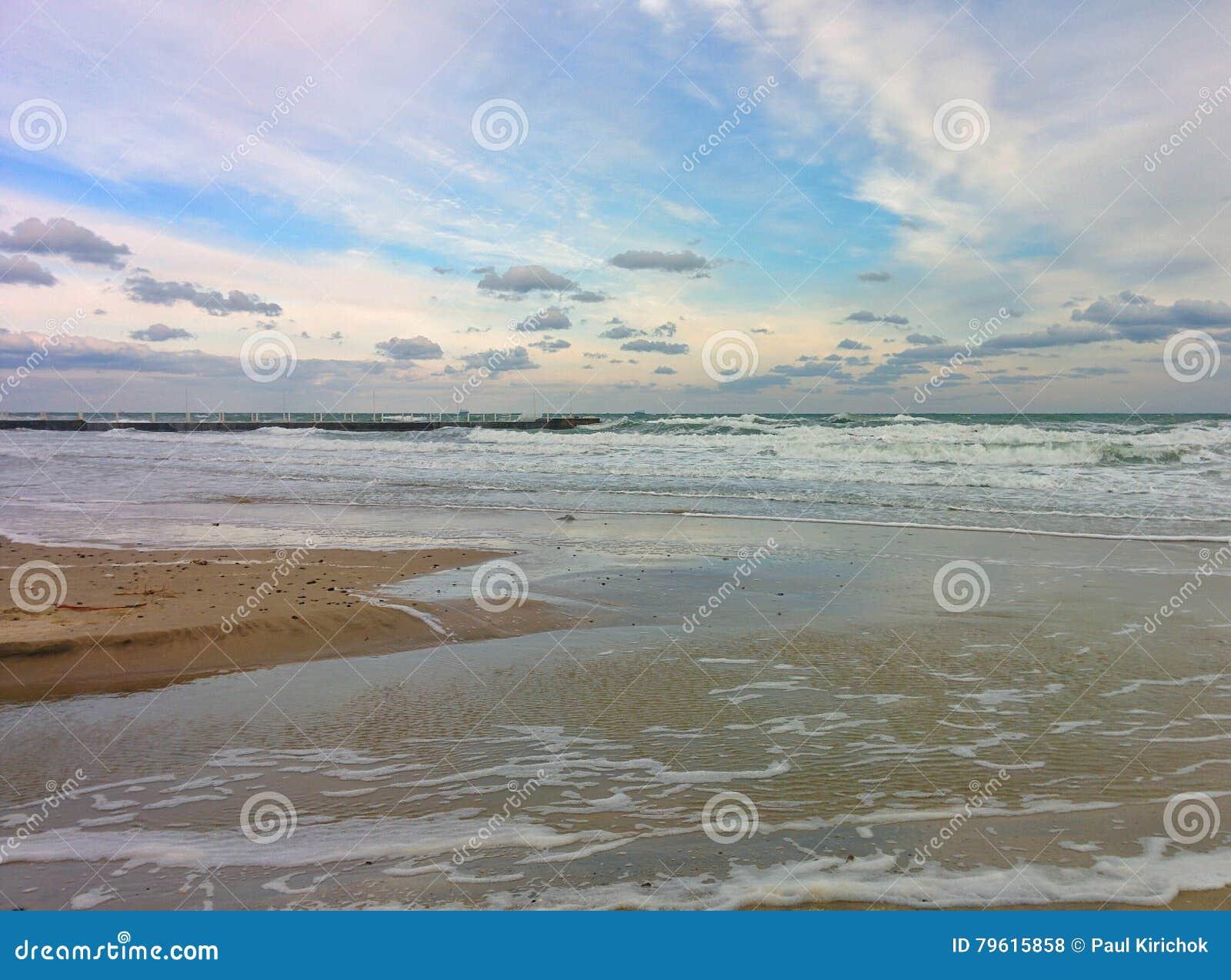 Seascape com praia da areia, o céu nebuloso e as ondas