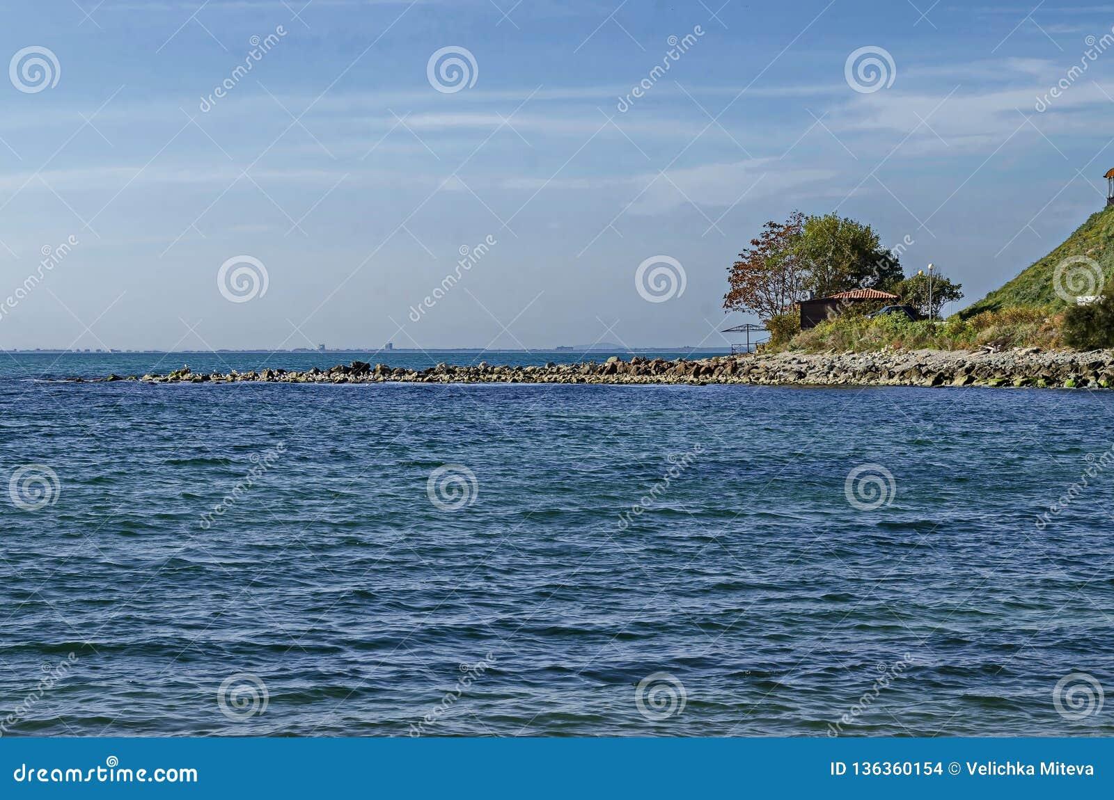 Seascape do cais para pescar no Mar Negro com larus, a casa pequena e a árvore na costa, cidade antiga Nessebar