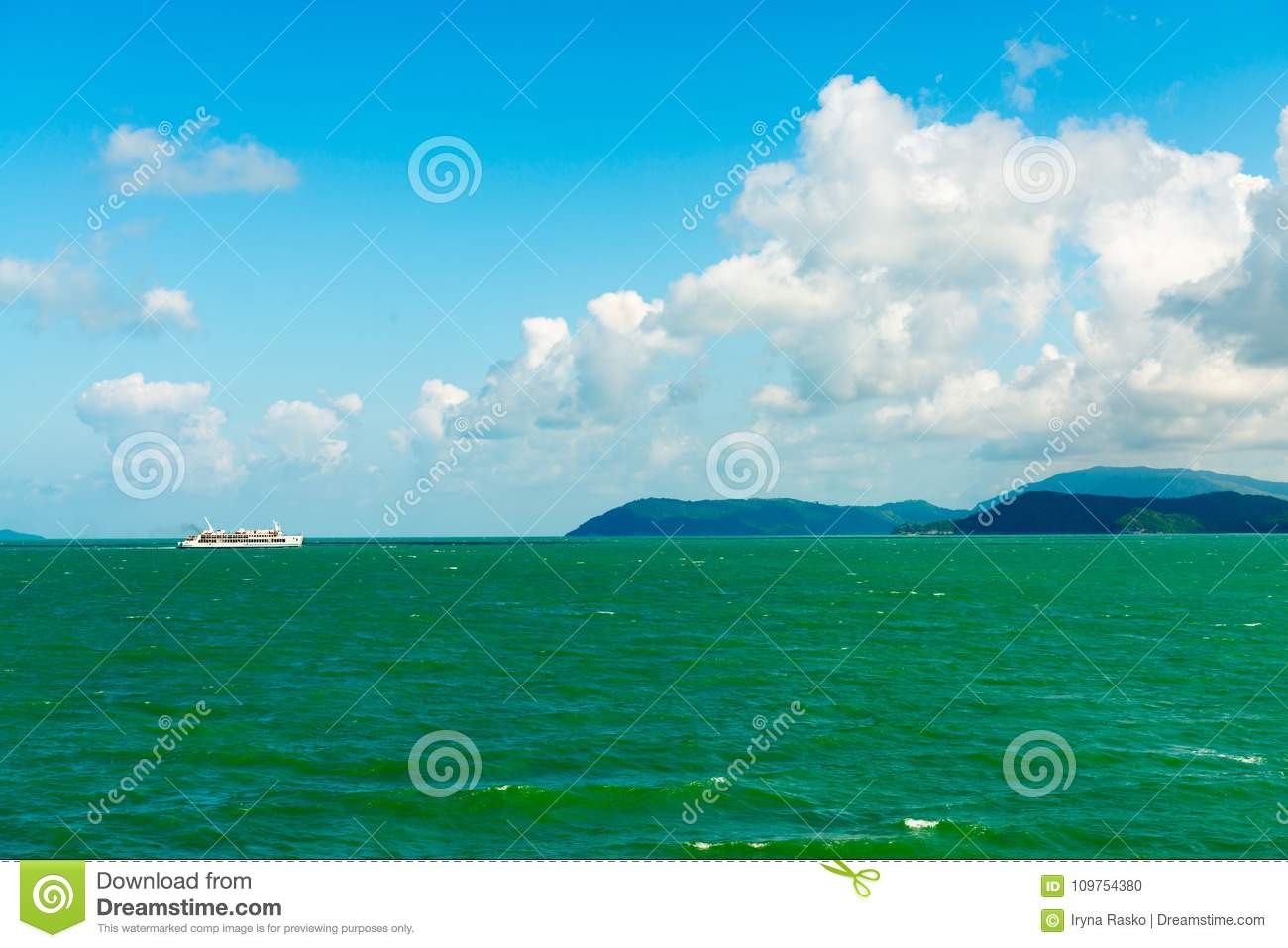 Seascape with white sea ferry and green islands on horizon