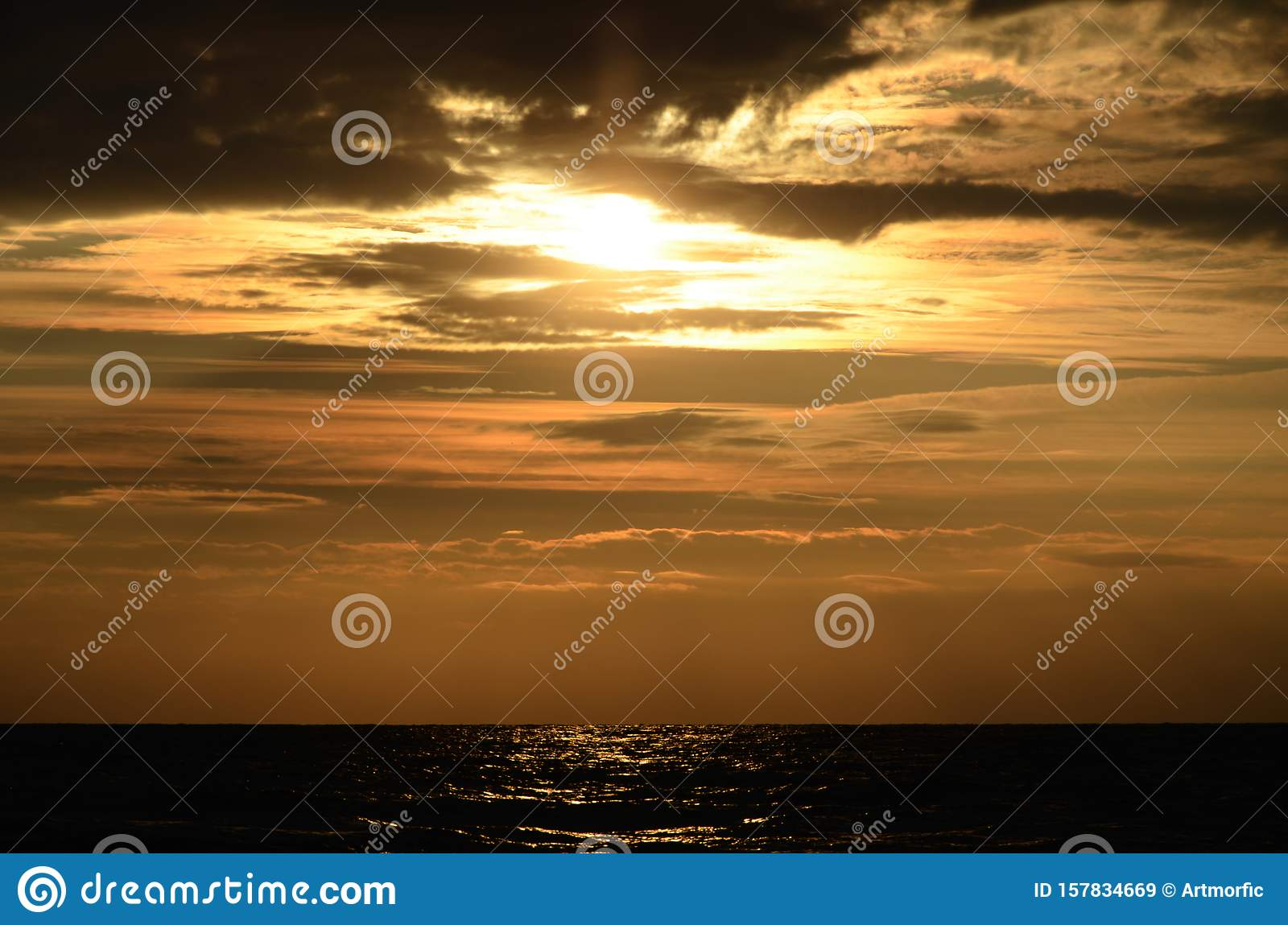 Seashore sky orange tones clouds and sea waves beautiful nature bright sunset dark water