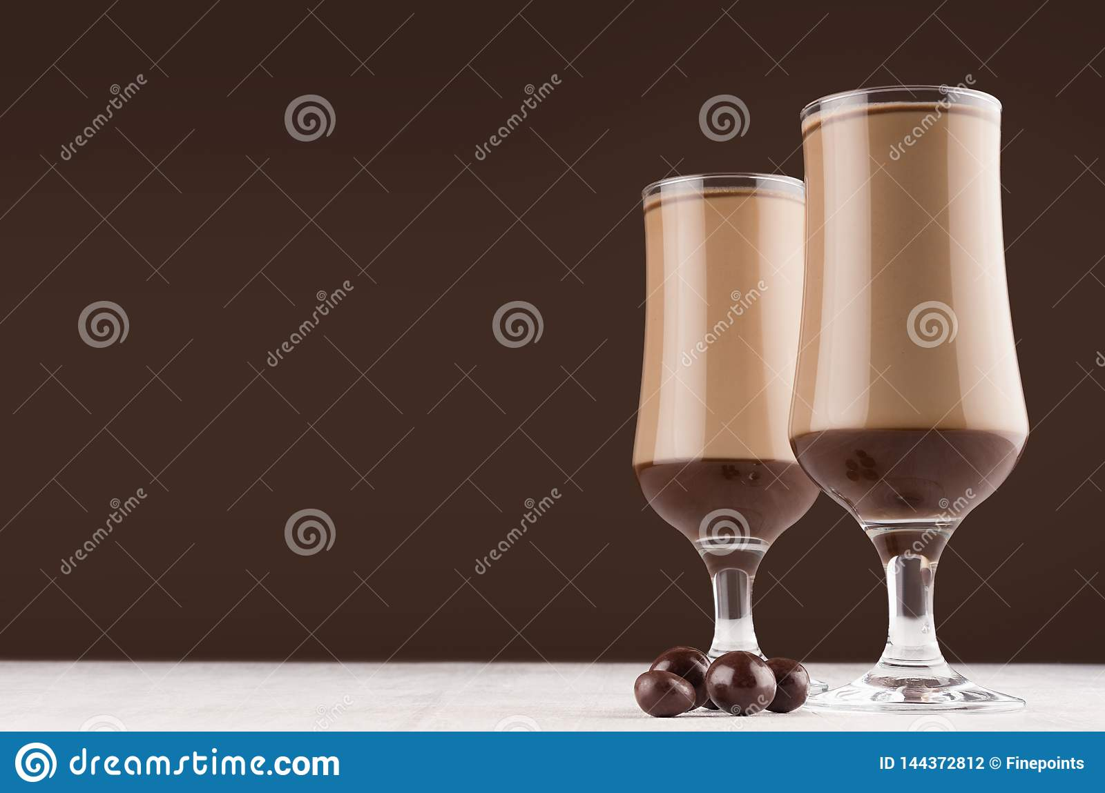Season coffee beverage in two glass with chocolate balls candies on dark brown wall and white wooden table, copy space.