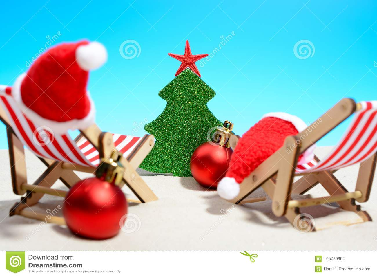 Seasonal Christmas greetings from a tropical beach with two deck chairs, Santa hats, baubles in red and white in front of a Xmas t