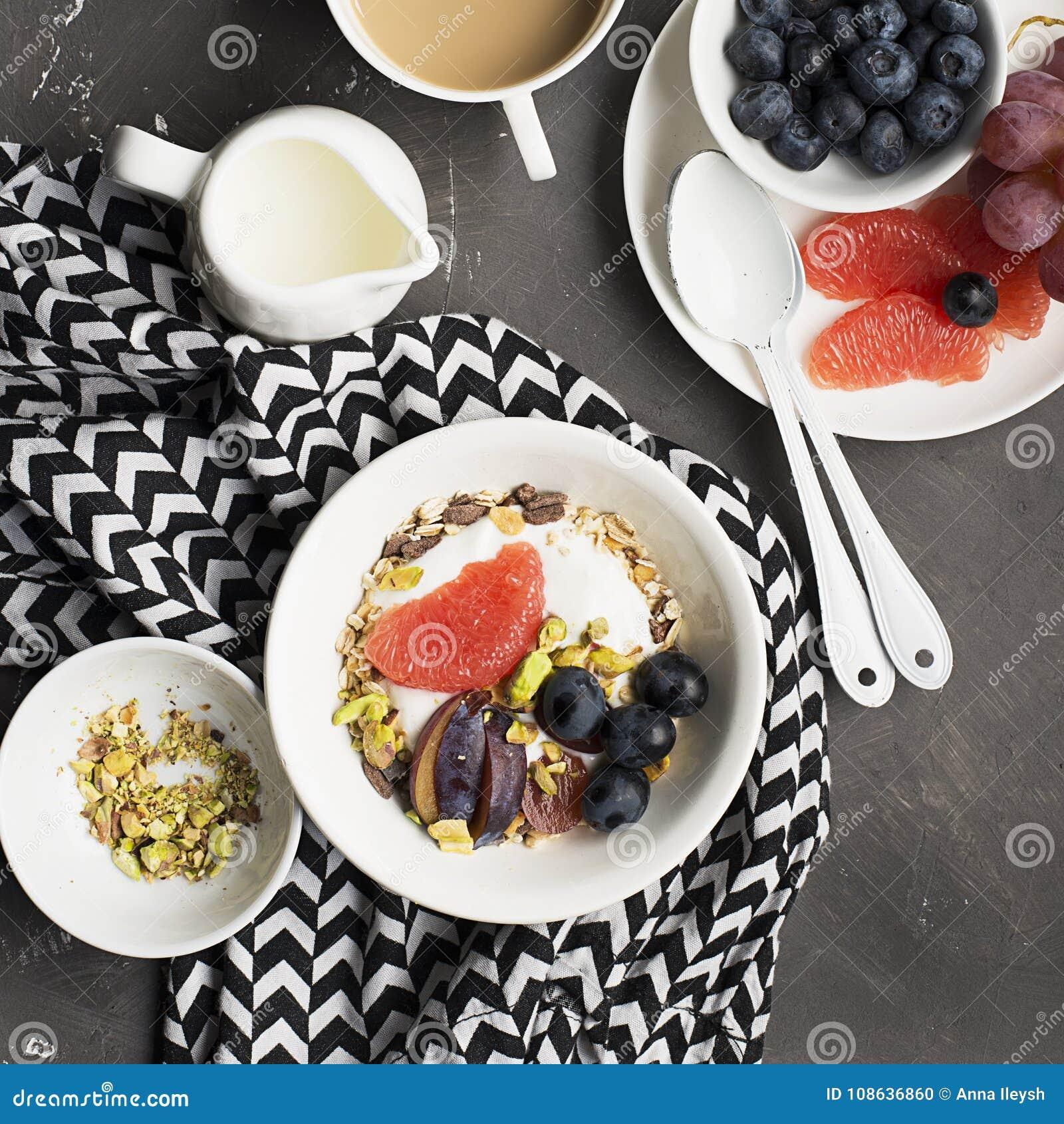 Seasonal healthy breakfast: yoghurt, chocolate granola, pink grapefruit, grapes, pistachios. Top view. Copy space. flat
