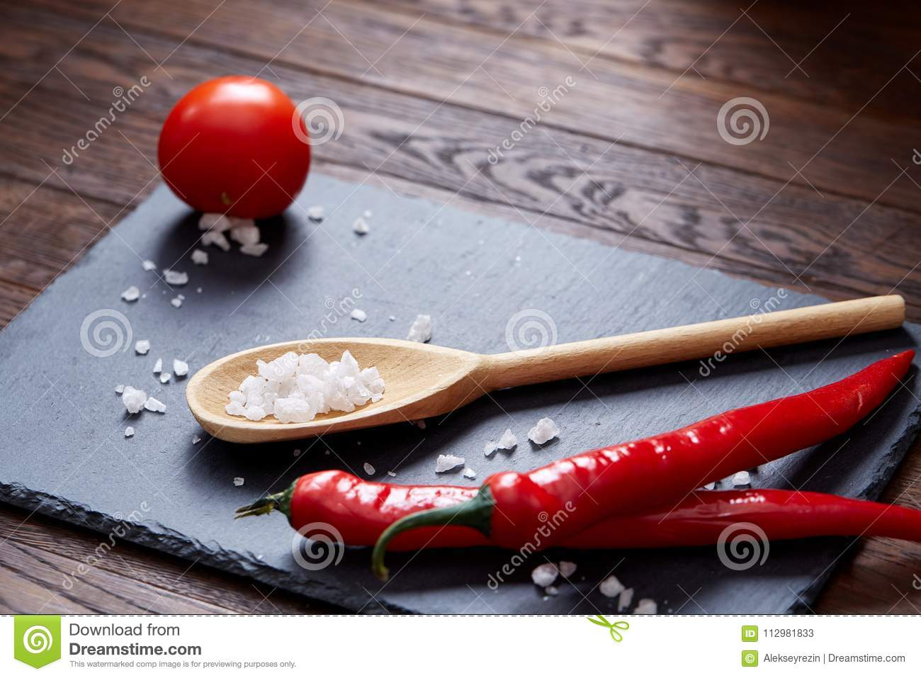 Vegetarian still life with fresh grape tomatoes, pepper and salt in wooden spoon on wooden background, selective focus