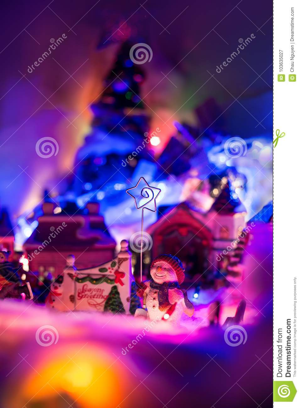 seasons greeting sign with smiling snowman holding star of bethlehem stands in front of a christmas
