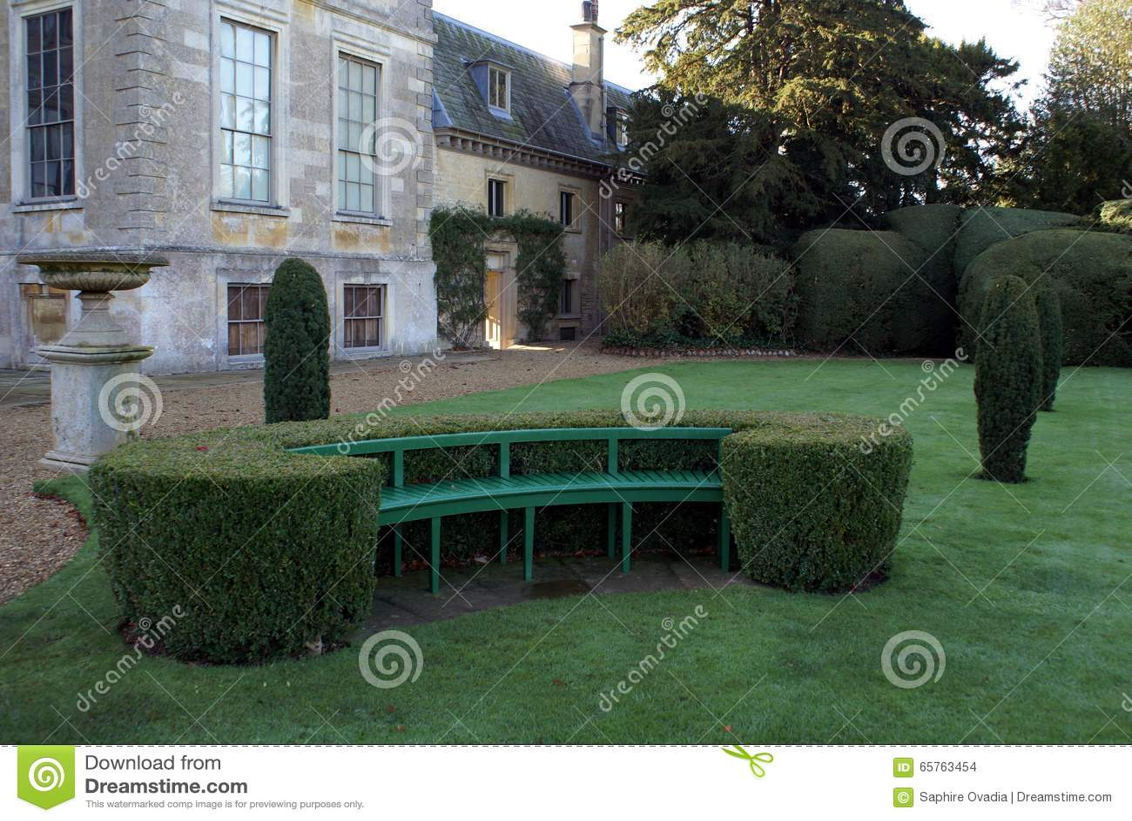 Seat byggde in i häckarbete och tappningurnan på en sockel i en trädgård