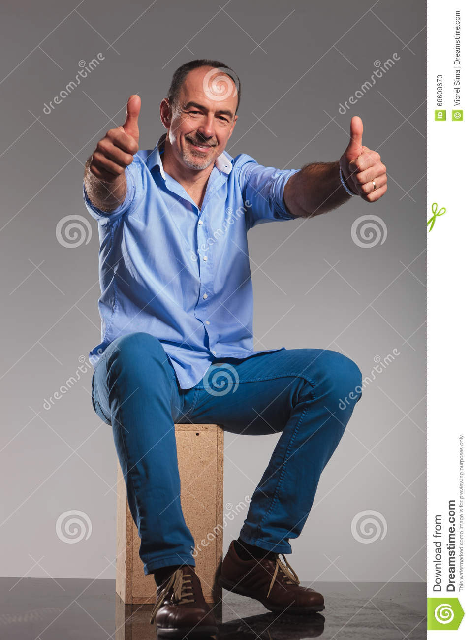 seated bearded mature man in jeans, showing thumbs up stock image