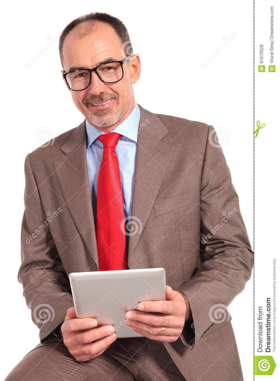 Seated old happy businessman holding a tablet pad